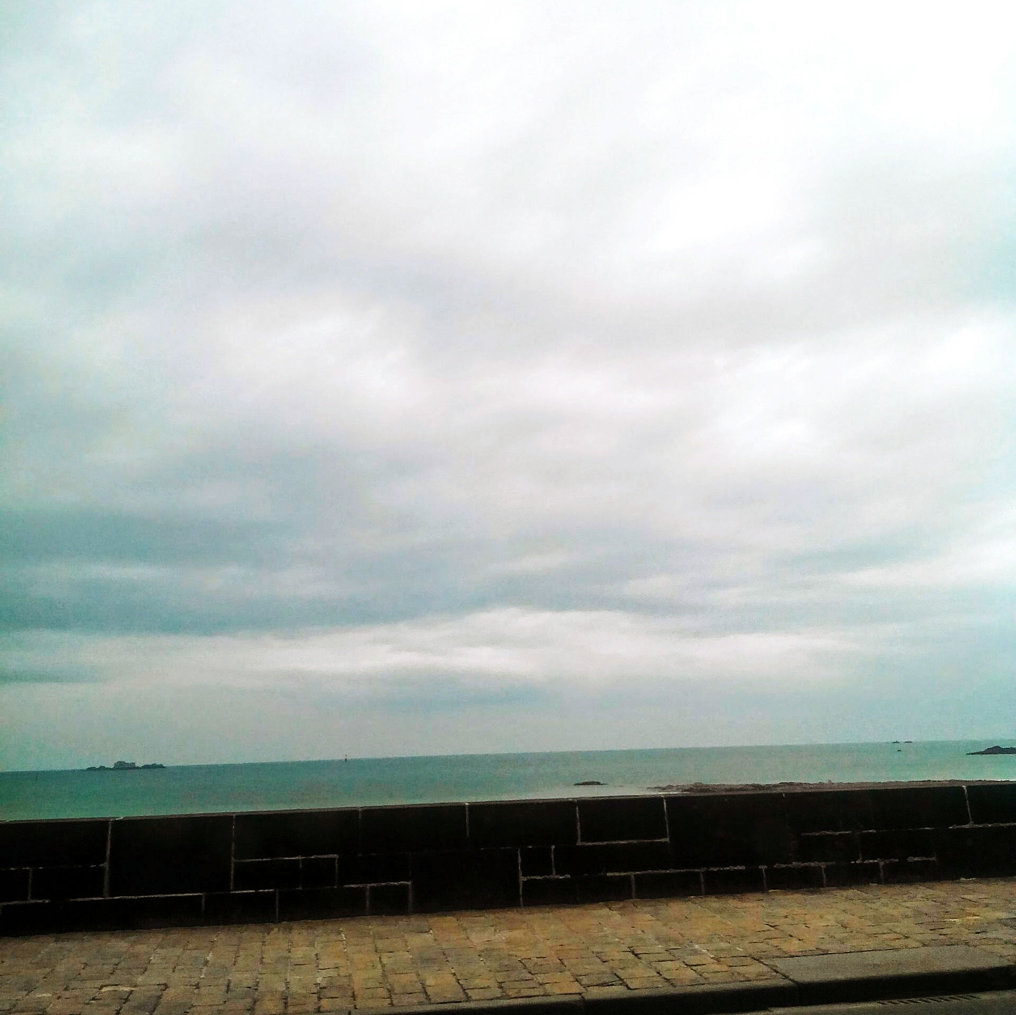 sea, sky, horizon over water, water, cloud - sky, tranquil scene, tranquility, cloudy, beach, scenics, beauty in nature, cloud, nature, overcast, shore, weather, railing, outdoors, built structure, day