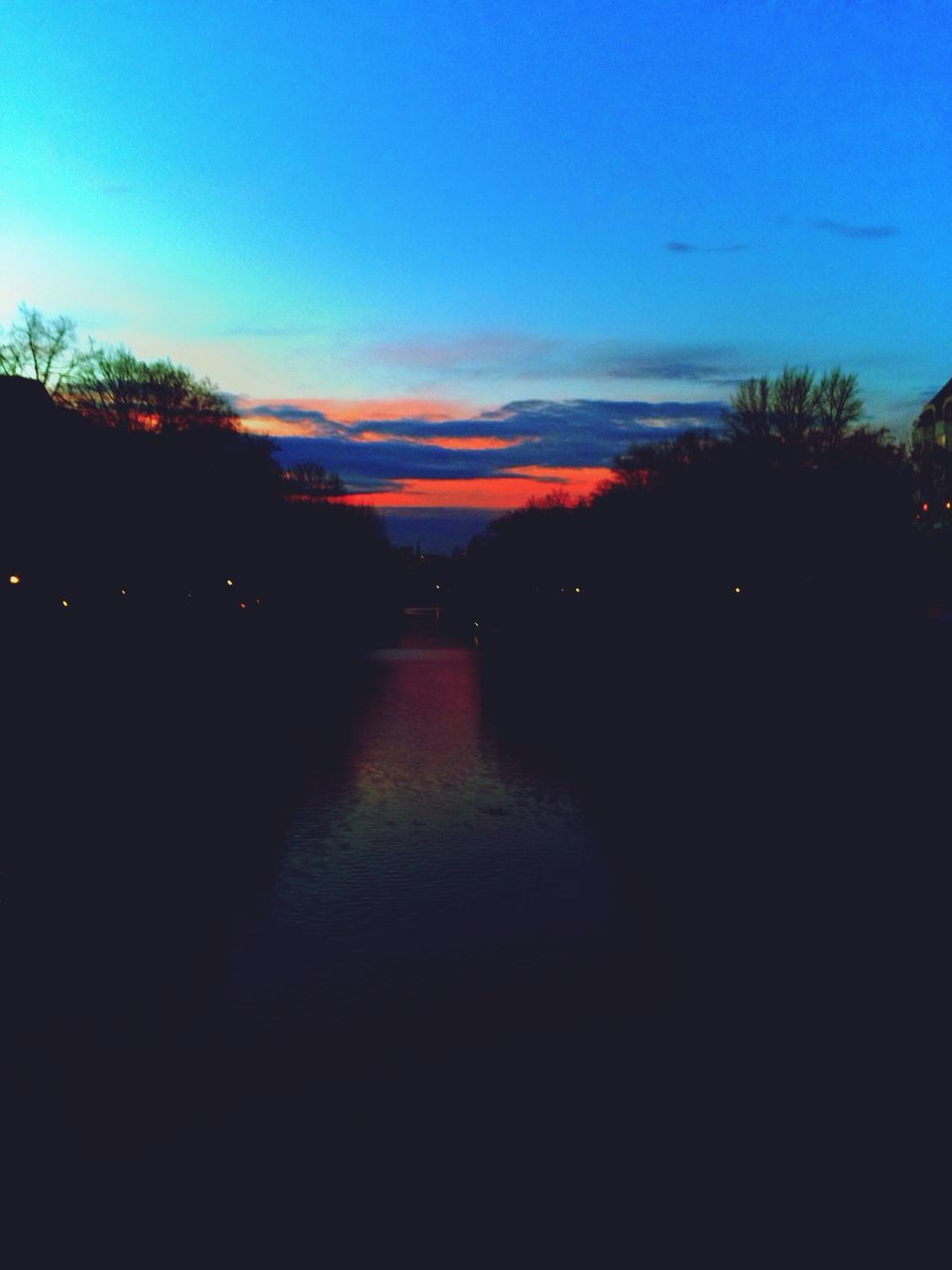 Canal Amidst Silhouette Trees Against Sky At Dusk
