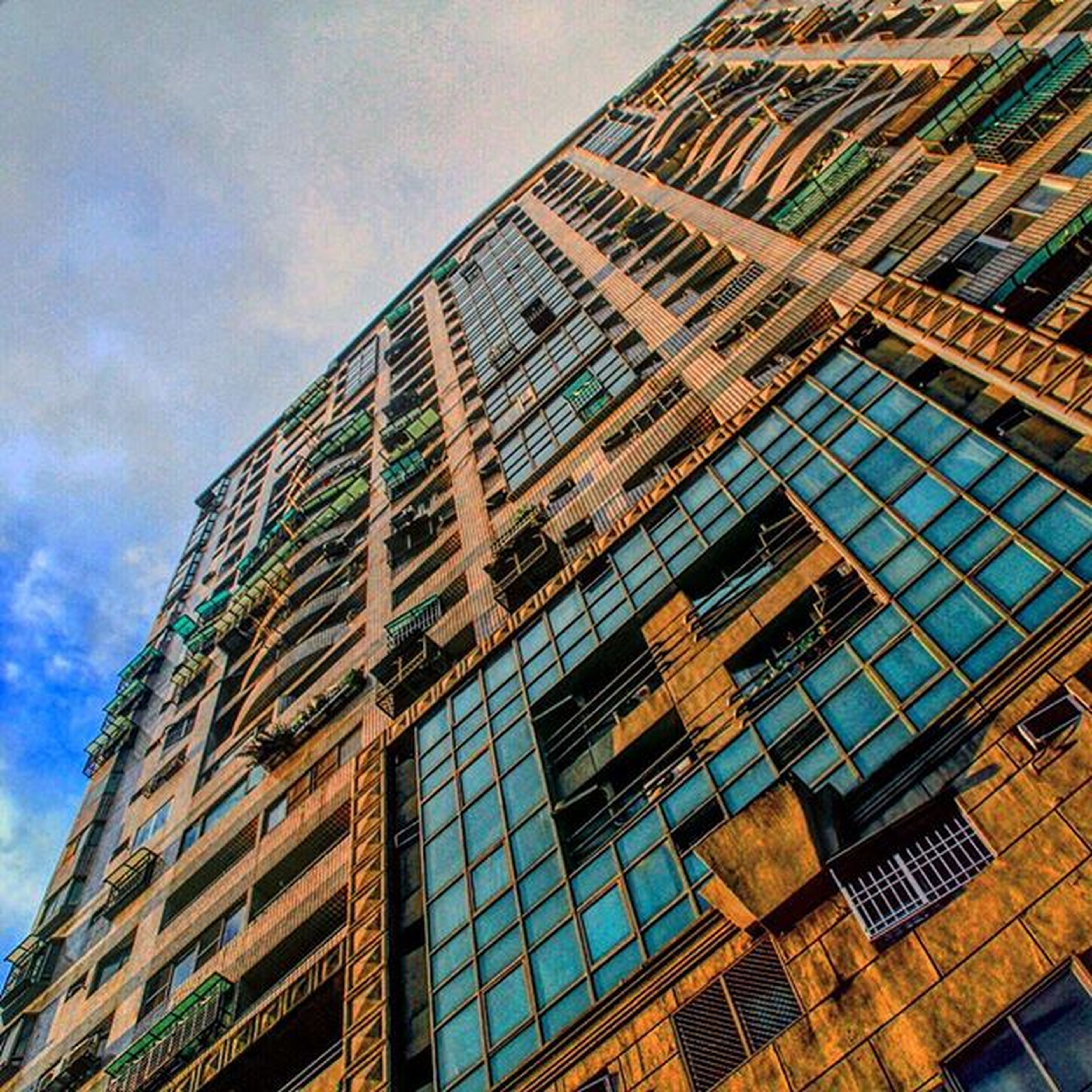 architecture, low angle view, built structure, building exterior, sky, window, building, glass - material, modern, cloud - sky, reflection, office building, day, city, no people, cloud, outdoors, residential building, residential structure, architectural feature