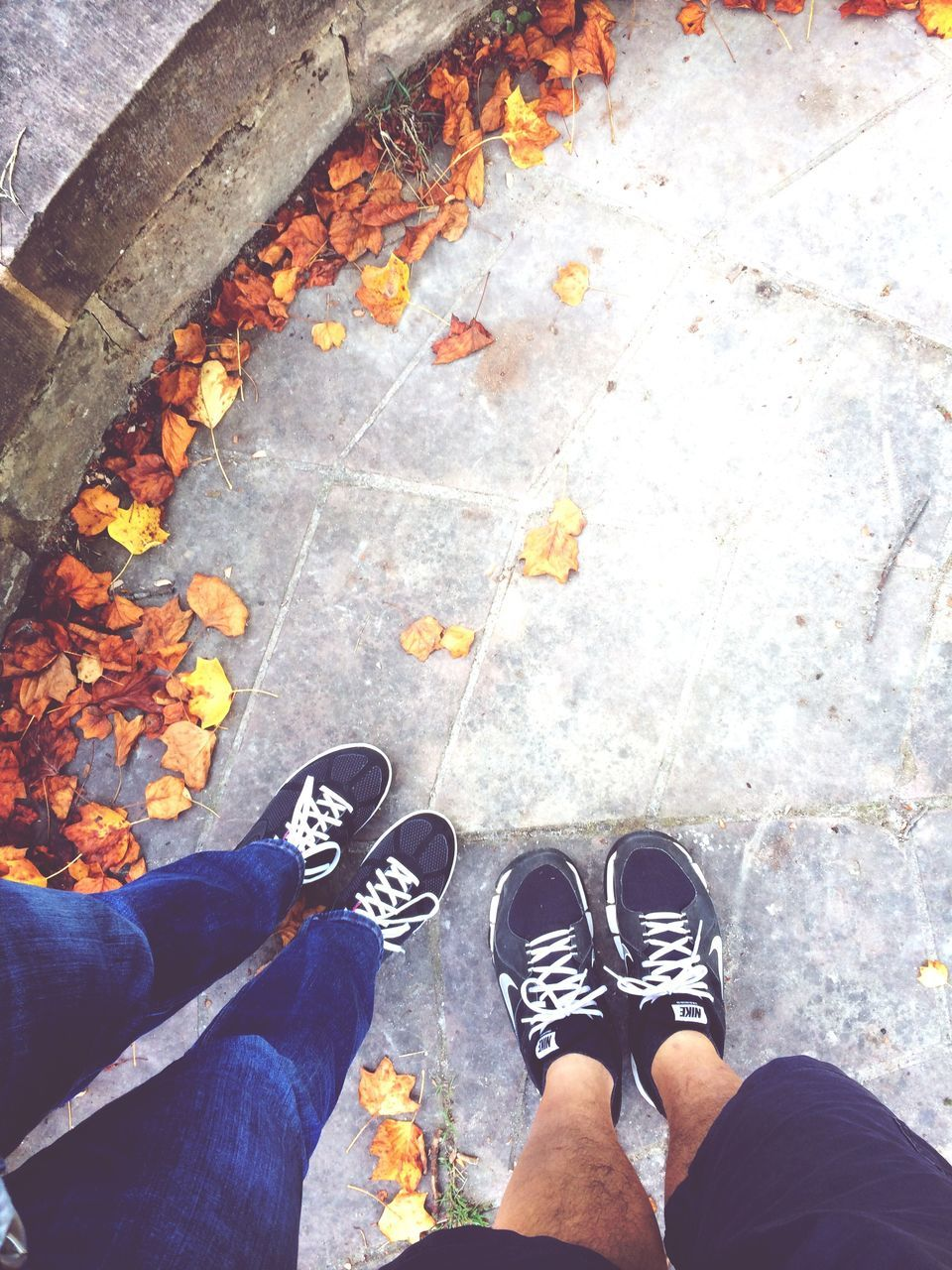 Low Section Of Couple Standing By Dry Autumn Leaves