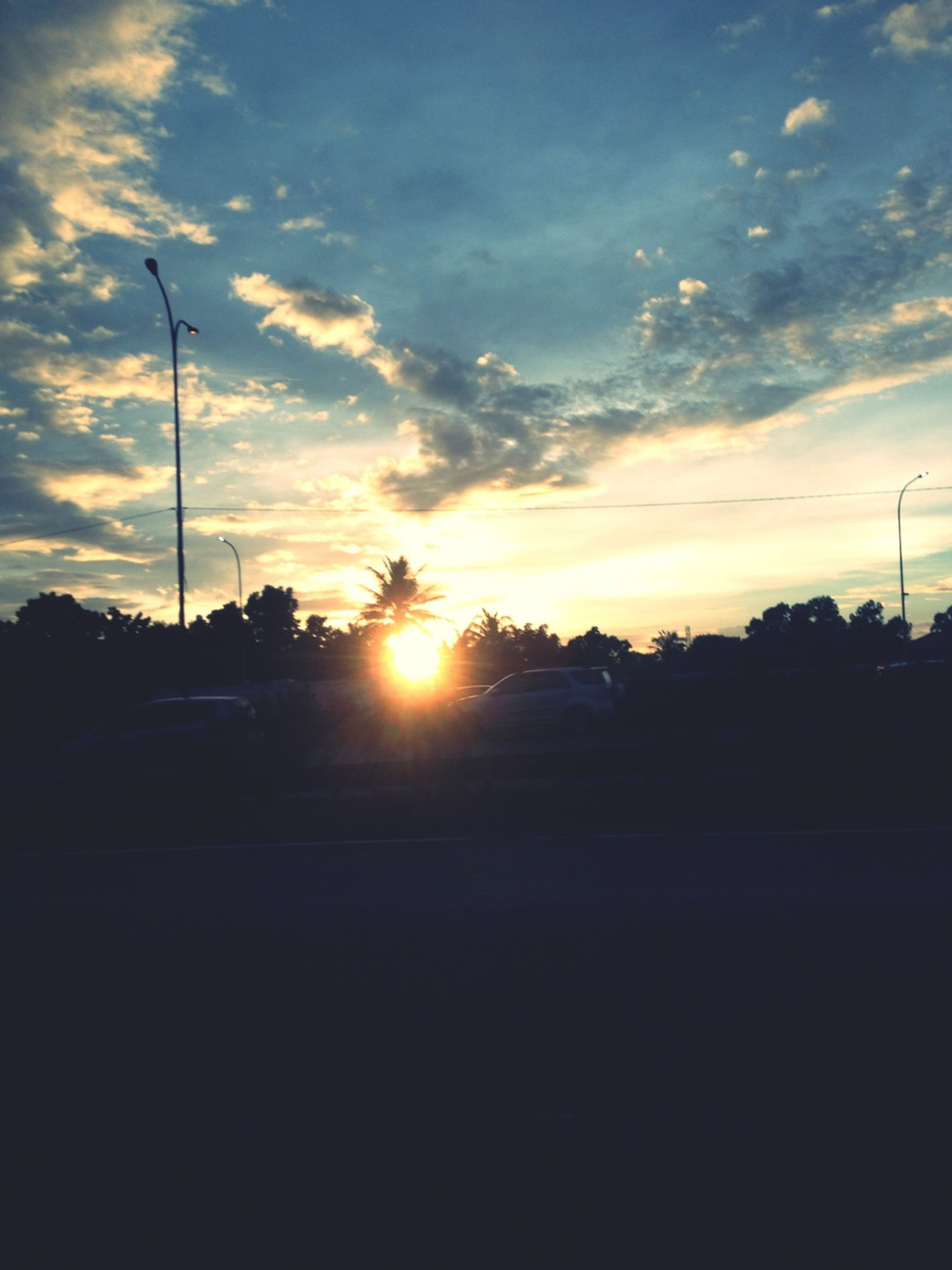sunset, silhouette, sun, sky, street light, cloud - sky, tree, orange color, sunlight, road, scenics, tranquility, tranquil scene, beauty in nature, nature, sunbeam, transportation, cloud, electricity pylon, dark