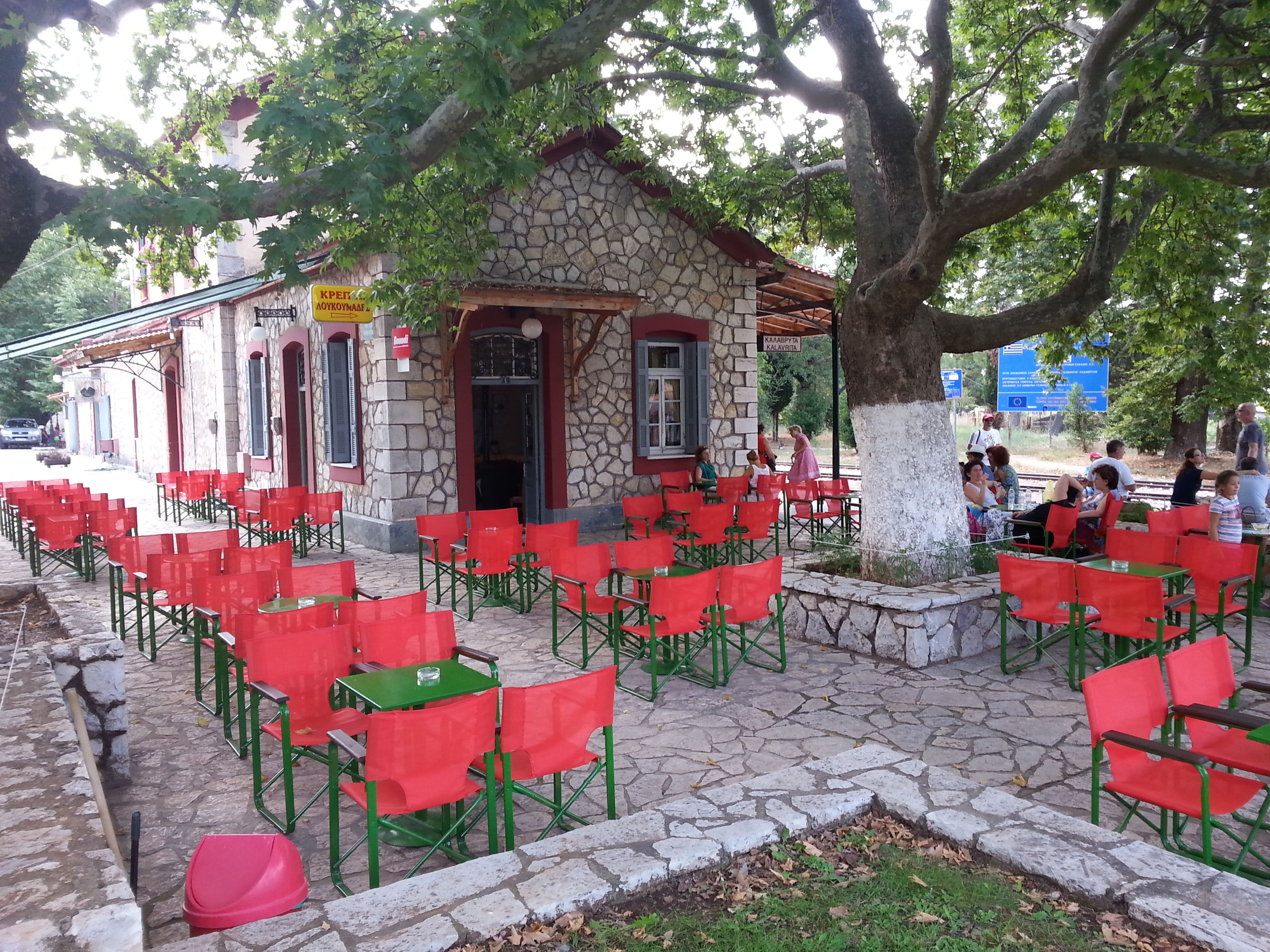 building exterior, architecture, built structure, tree, red, street, day, house, outdoors, potted plant, cobblestone, city, incidental people, sidewalk, footpath, sunlight, in a row, residential structure, chair, residential building