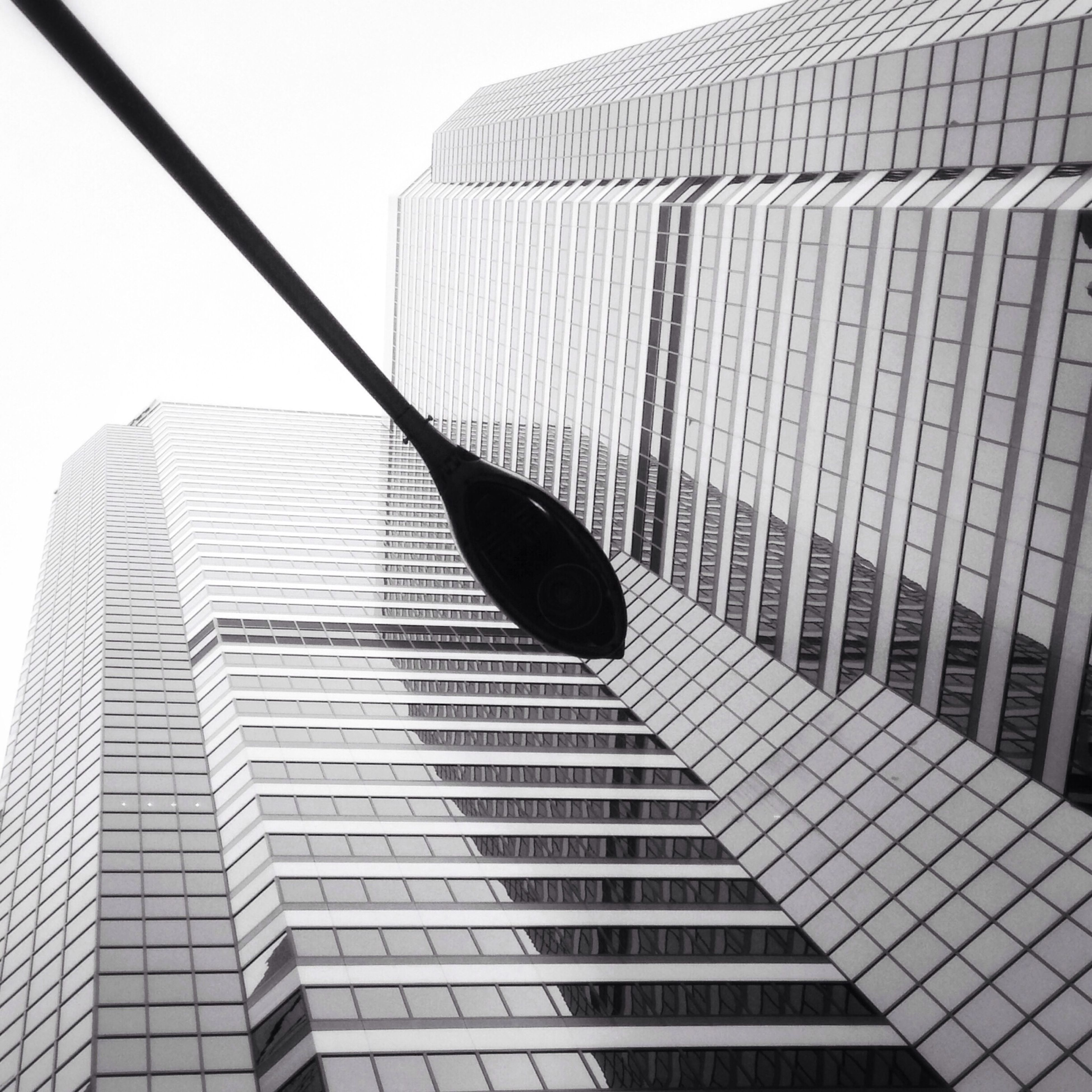 low angle view, building exterior, architecture, modern, built structure, office building, skyscraper, clear sky, city, tall - high, building, pattern, glass - material, day, tower, no people, outdoors, sky, window, reflection