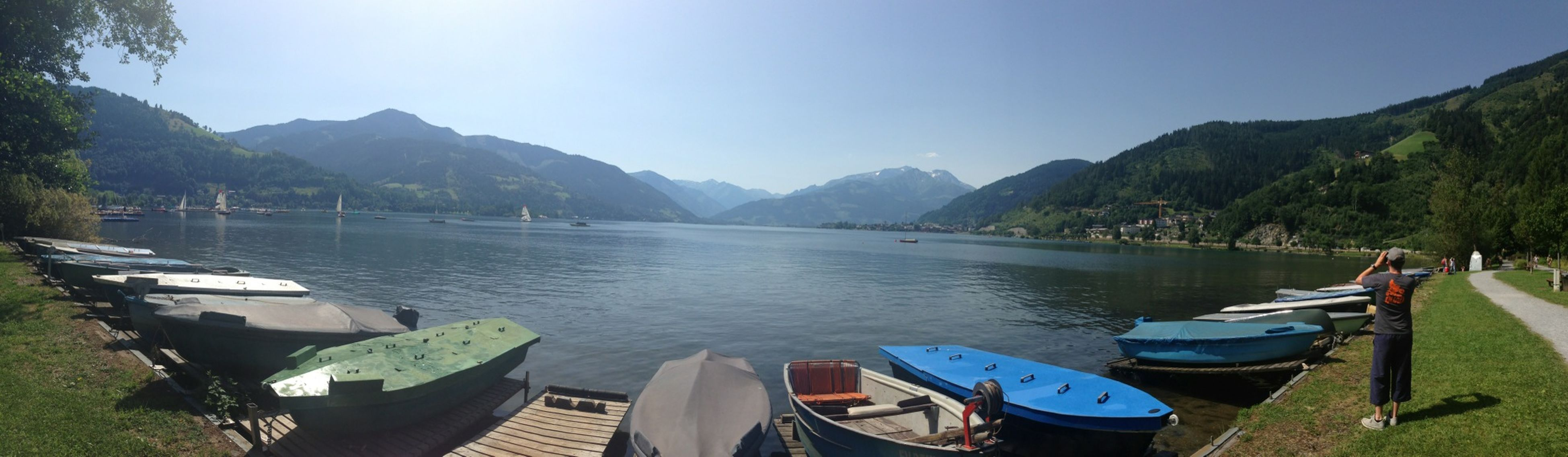 mountain, water, nautical vessel, mountain range, moored, scenics, tranquil scene, lake, tranquility, transportation, boat, clear sky, sky, beauty in nature, tree, nature, mode of transport, sunlight, river, day