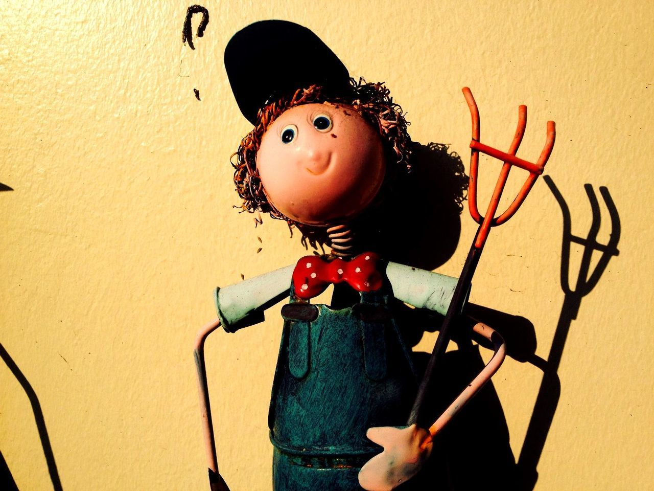 Character holding rake against yellow wall