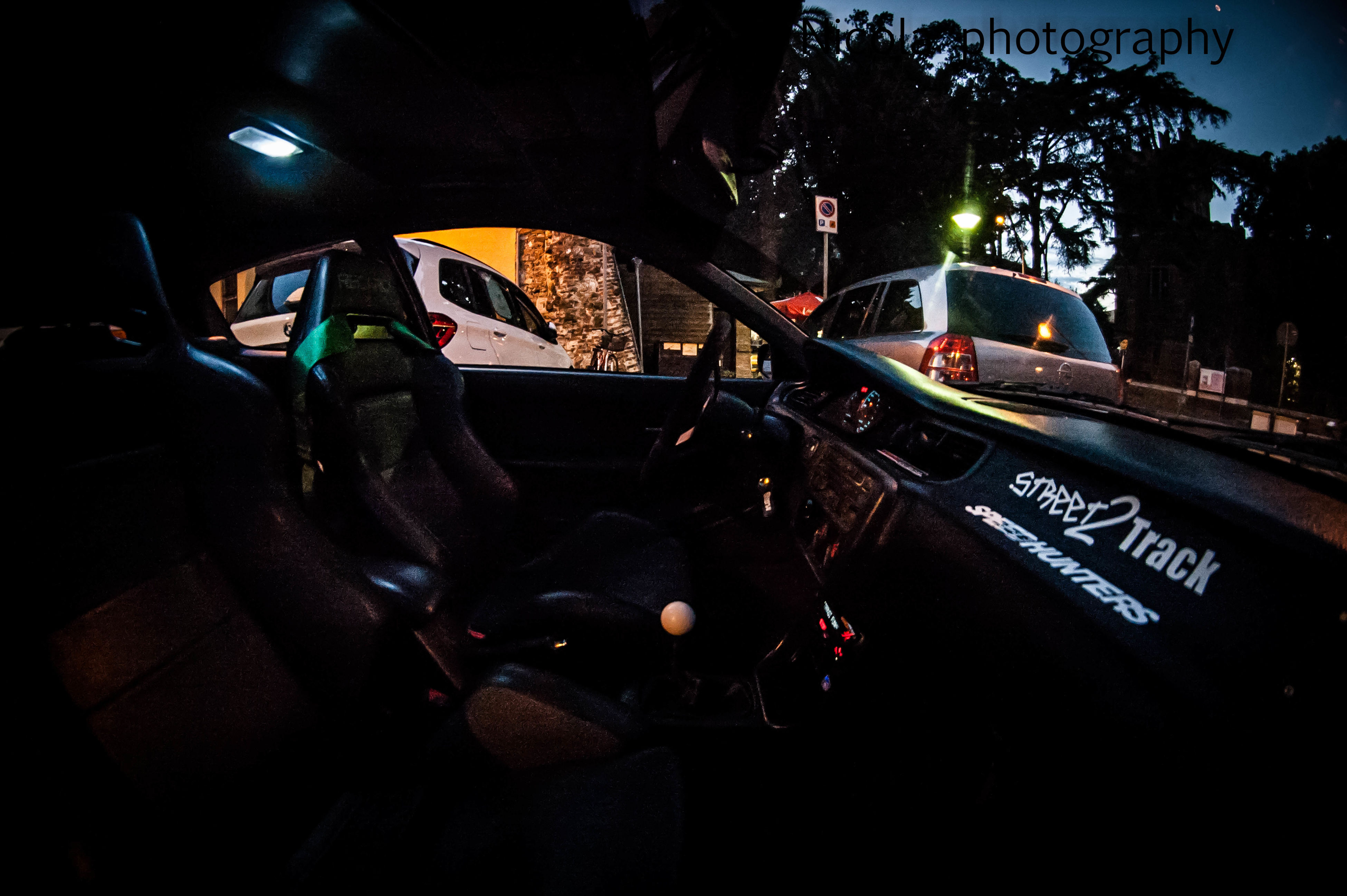 land vehicle, mode of transport, car, transportation, illuminated, car interior, dashboard, street, night, travel, road, vehicle interior, parking, motorcycle, roadside, parked, stationary, road trip, tail light, vehicle, person
