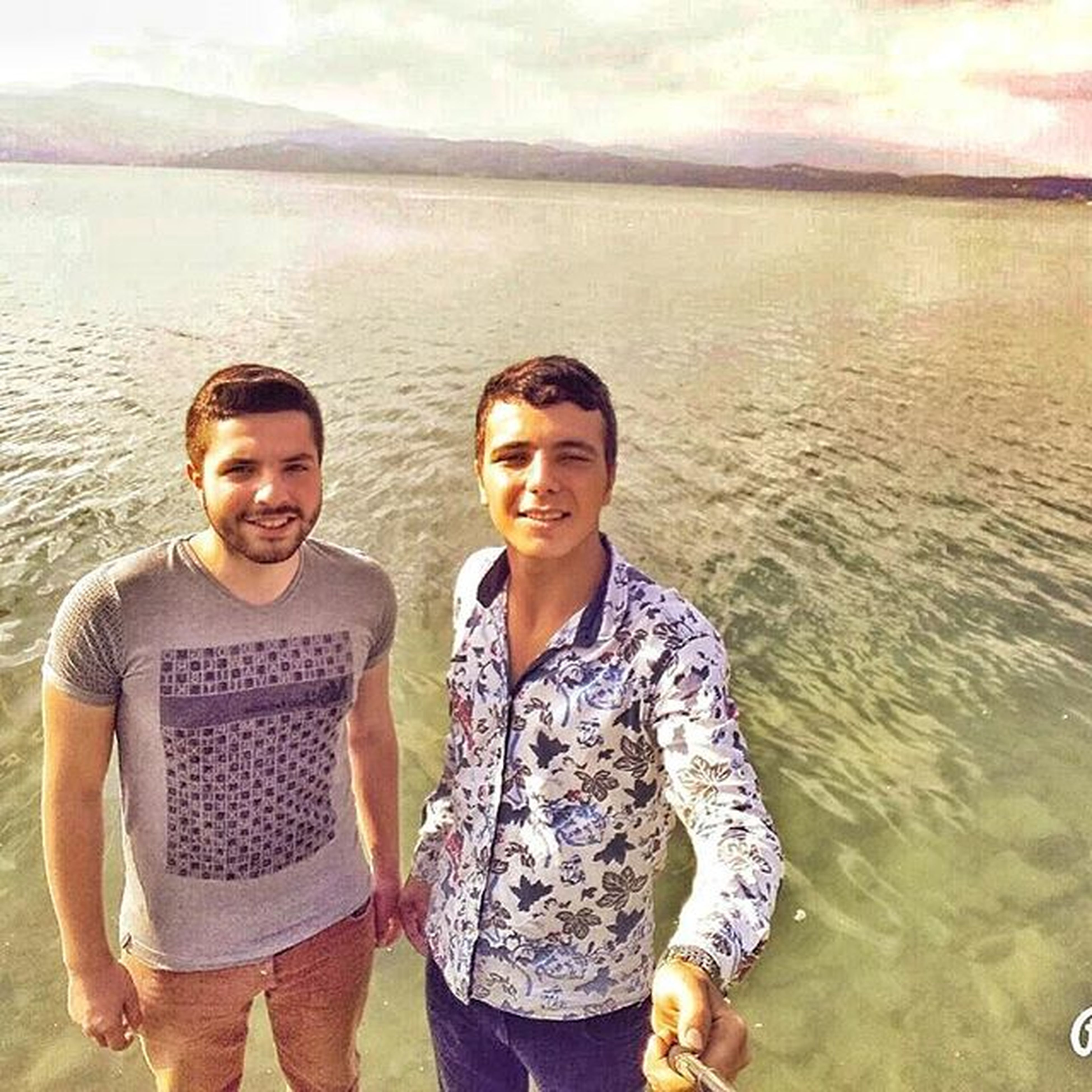 lifestyles, person, looking at camera, portrait, leisure activity, smiling, togetherness, water, bonding, happiness, casual clothing, front view, young adult, love, standing, young men, toothy smile