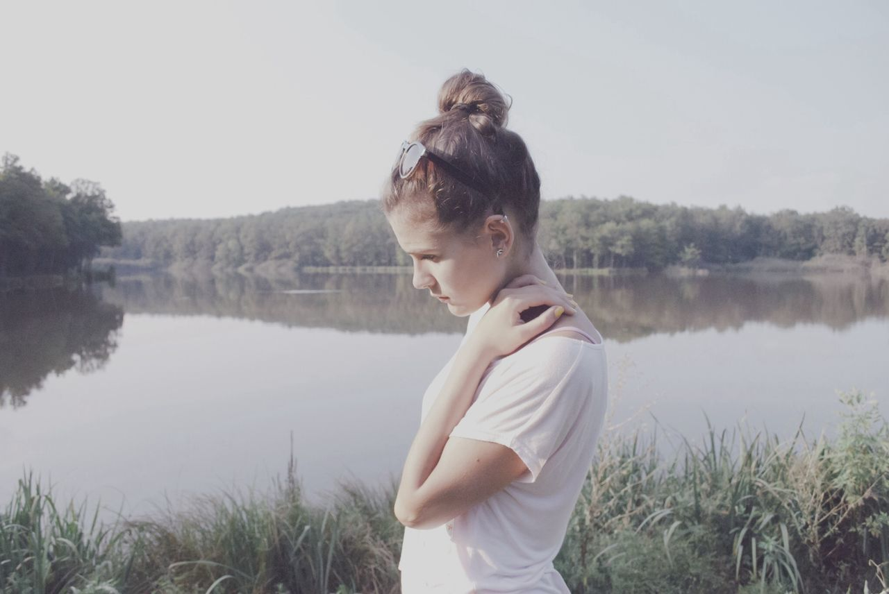 Side view of beautiful young woman standing on lake shore