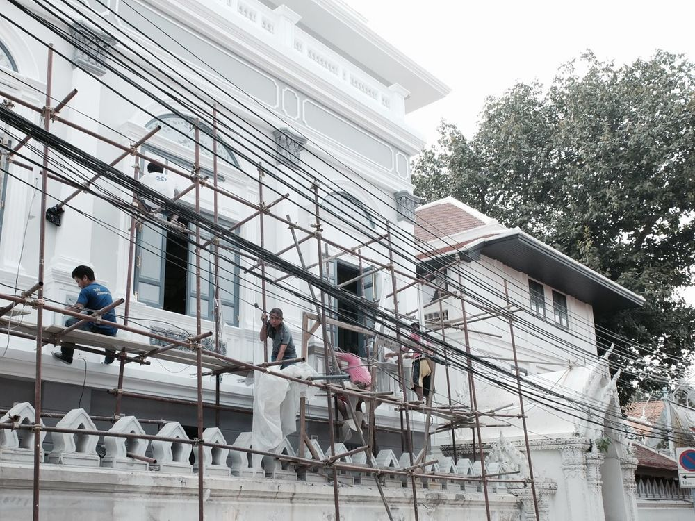 Workers at work in Bangkok Rattanakosin district near the Grand Palace. Architecture Bangkok Built Structure Colonial Architecture Medium Group Of People Old Town Rattanakosin Renovation Scaffold Scaffolding Thai People Thailand Villa Workers Workers At Work Workworkwork
