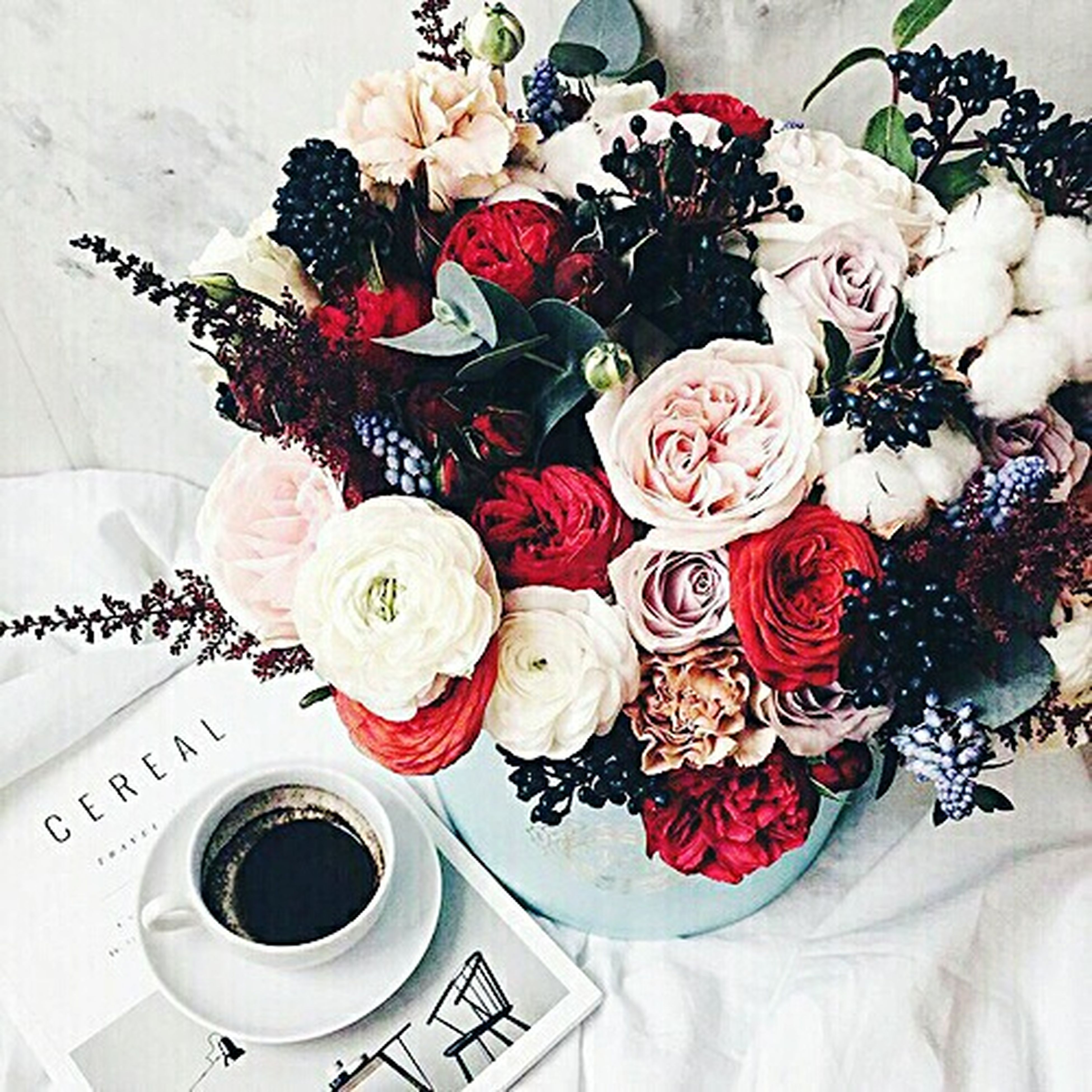 indoors, flower, freshness, table, coffee cup, food and drink, vase, high angle view, drink, coffee - drink, refreshment, still life, plate, cup, saucer, one person, rose - flower, food, sweet food, coffee