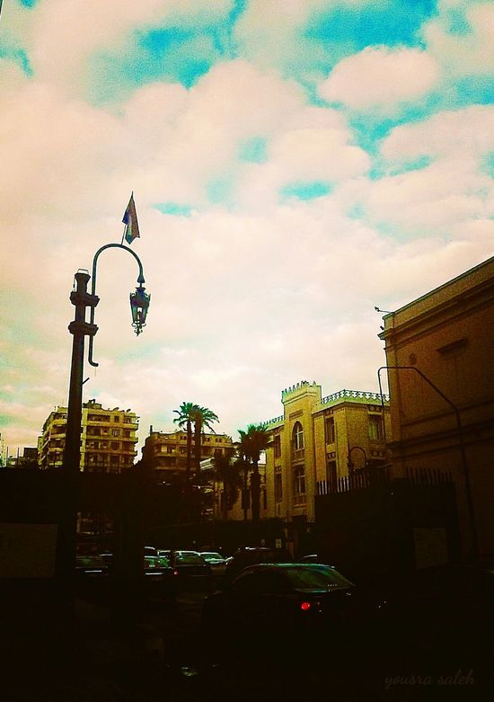 Cloudy Day Clouds And Sky Clouds Blue Sky Blue Sky And Clouds Cars Cars Lights Cars On The Street Cars On The Road!!Traffic Flow City City Life City Street Streetphotography Street Photography Building And Sky Building Structures Palms In The City Street Lamp Electric Lamp Flag Of Egypt Outdoorsphotograph Architecture Cairo Egypt Love To Take Photos ❤
