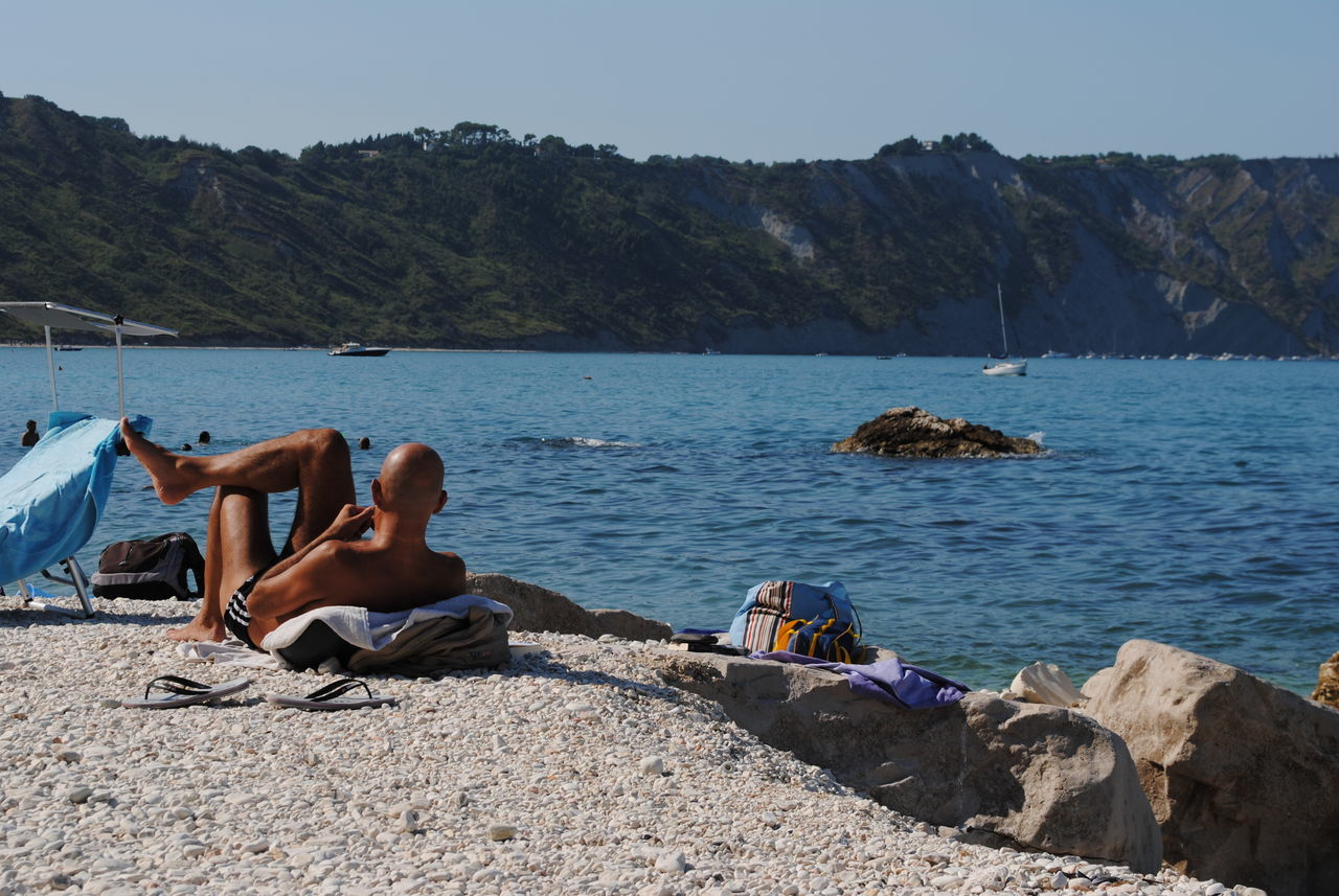 man relaxing on the beach in Italy Adult Adults Only Beach Man Nature Outdoors People Relaxation Rock Sea And Sky Vacations Water Young Adult