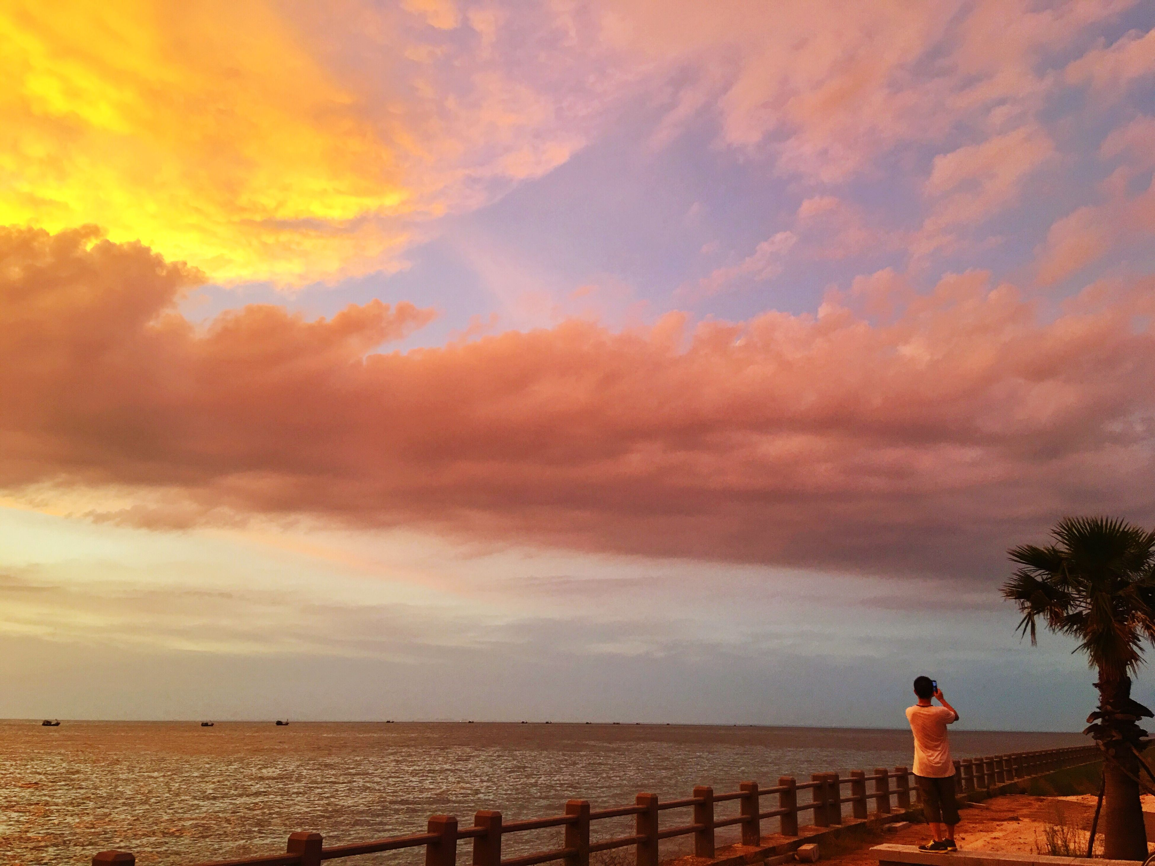 sea, sky, horizon over water, beach, water, leisure activity, lifestyles, cloud - sky, scenics, tranquility, beauty in nature, sunset, tranquil scene, shore, nature, railing, person, idyllic
