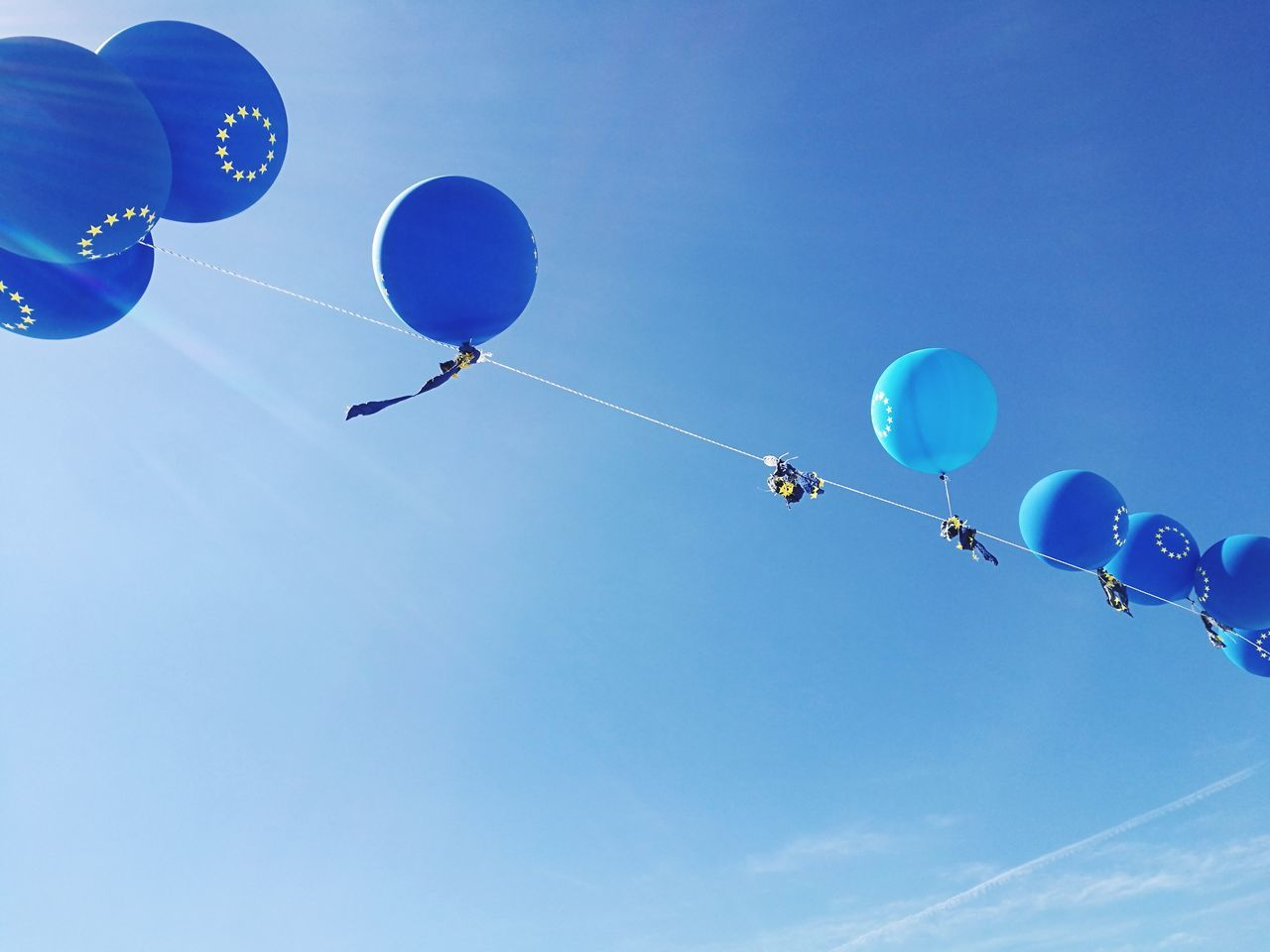balloon, low angle view, helium balloon, celebration, mid-air, helium, flying, blue, multi colored, party - social event, outdoors, day, sky, hot air balloon, ballooning festival, no people