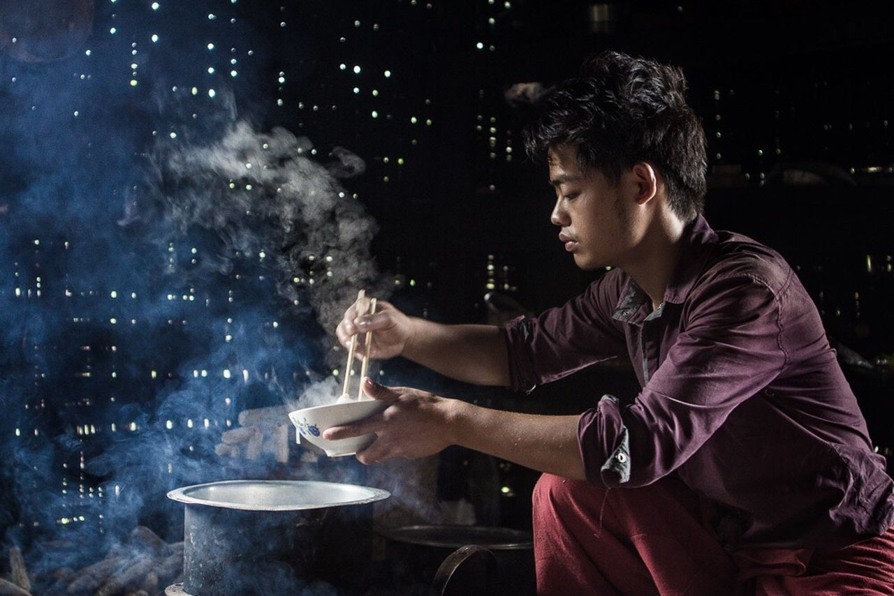 real people, preparation, one person, casual clothing, side view, night, food and drink, food, indoors, standing, young adult, freshness, people