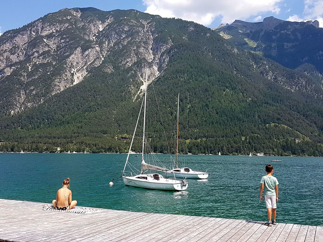 Sun seekers enjoy peaceful moments next to Lake Achen (Achensee) in Tyrol, Austria with sailboats lying at anchor. Achensee Alpine Lake Beauty In Nature Lake Lake Achen Leisure Activity Nautical Vessel People In The Sun Pertisau Sailboat Sailing Sunbathing Tranquil Scene Vacations