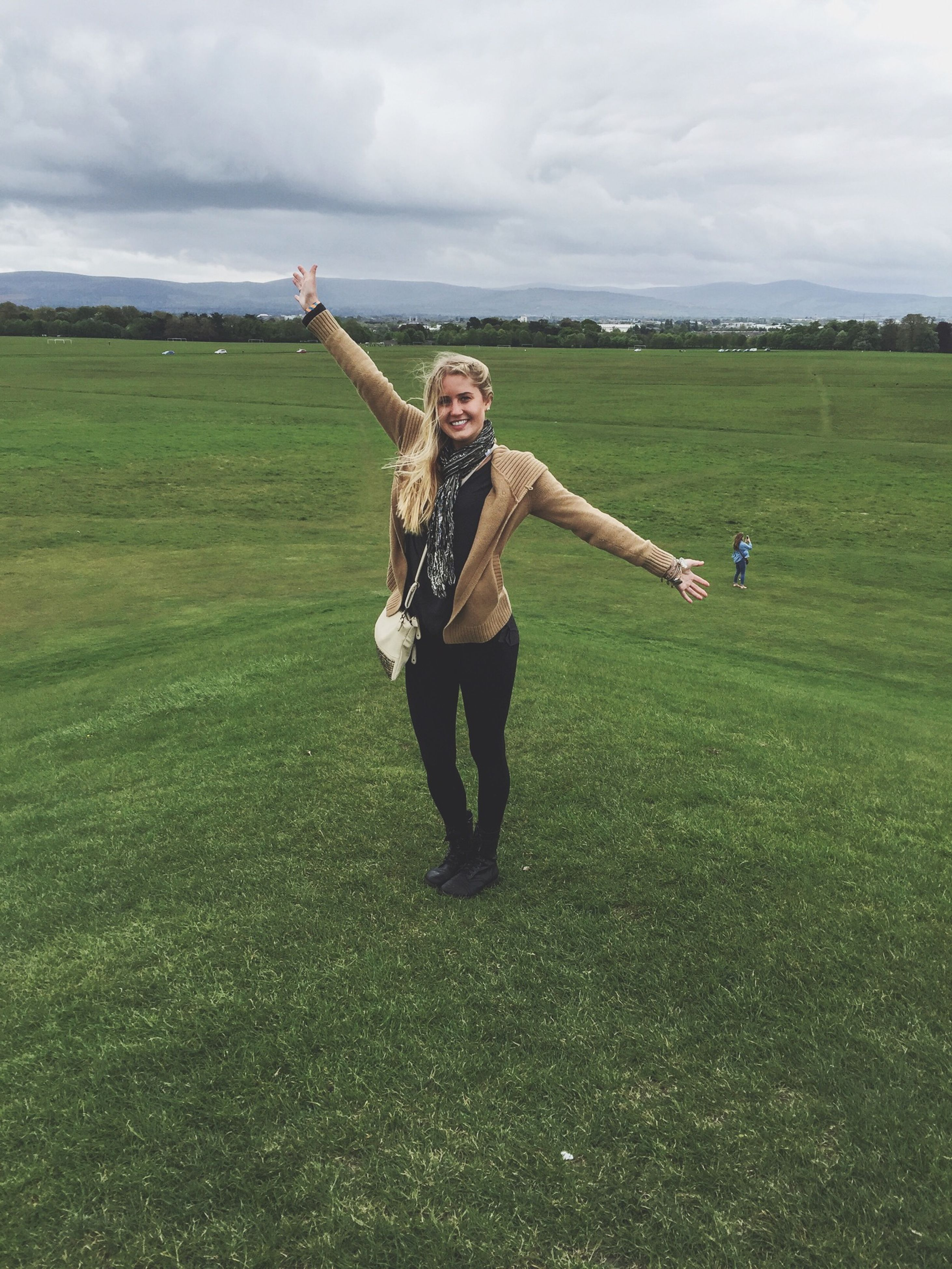 full length, grass, person, lifestyles, young adult, leisure activity, casual clothing, sky, field, happiness, young women, smiling, portrait, standing, looking at camera, front view, grassy, cloud - sky