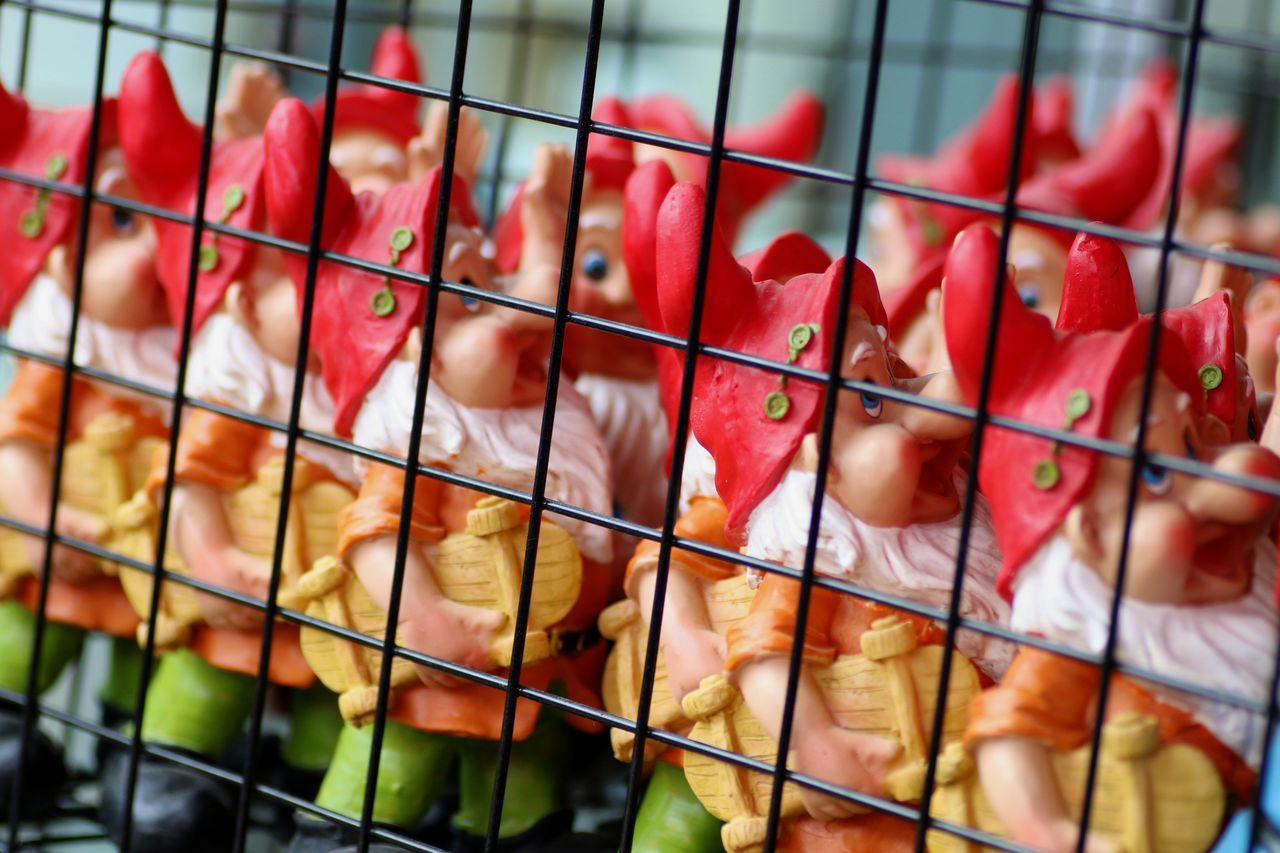 Animal Themes Cage Caged Close-up Day Decoration Dwarf Prison Dwarves Garden Gnomes Locked In Market No People Red Hats Retail  Trapped
