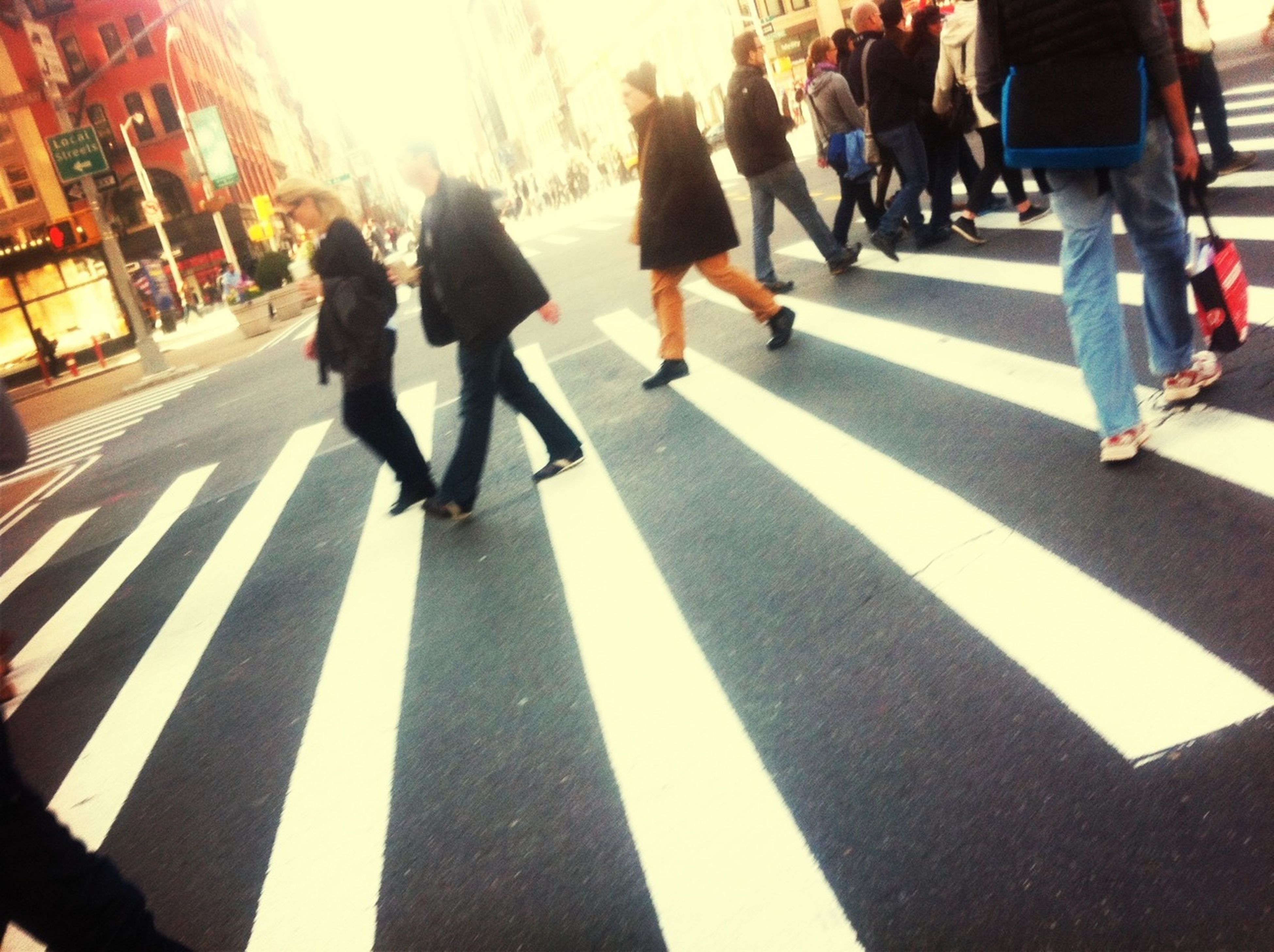 men, lifestyles, walking, person, city life, large group of people, leisure activity, street, city, medium group of people, zebra crossing, full length, togetherness, rear view, on the move, shadow, road marking, group of people, casual clothing