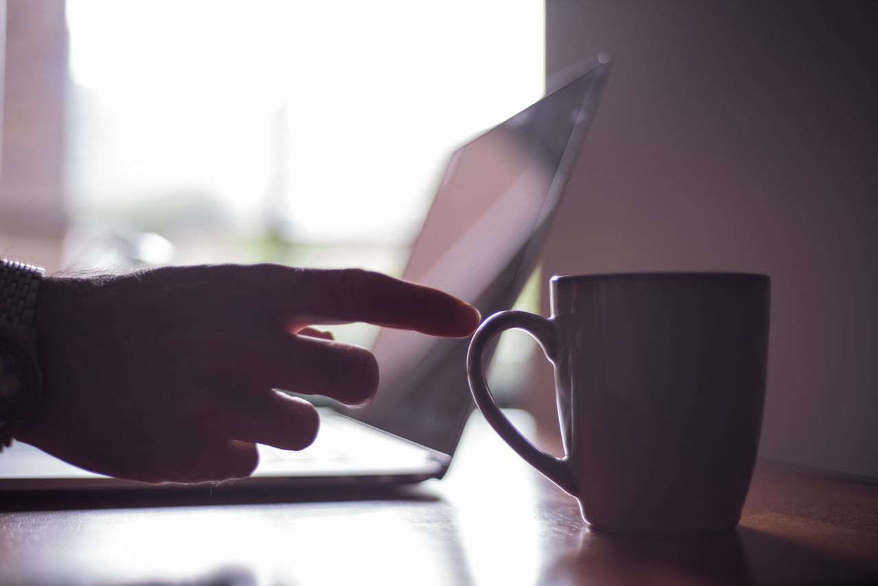 Reaching for morning coffee Atmosphere Atoms Coffee Desk Focus On Foreground Hand Laptop Lifestyles Morning Mug Office Part Of Person Professional Reaching Smart Phone Unrecognizable Person Wireless Technology Work