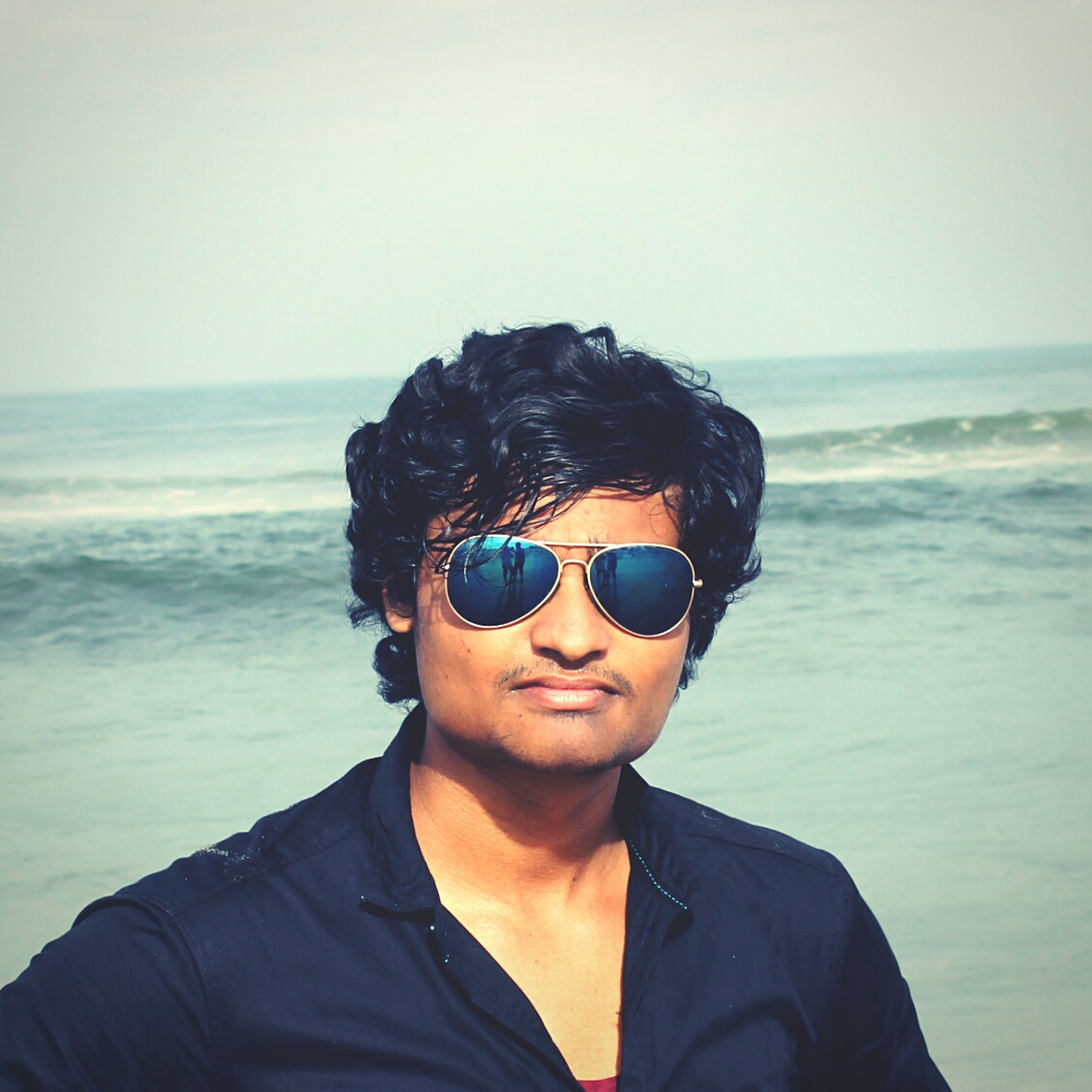 sea, young men, young adult, horizon over water, lifestyles, leisure activity, headshot, sunglasses, water, smiling, front view, casual clothing, clear sky, looking at camera, handsome, person, tranquility, scenics, nature, relaxation, summer, sunny, beauty in nature, focus on foreground, tranquil scene