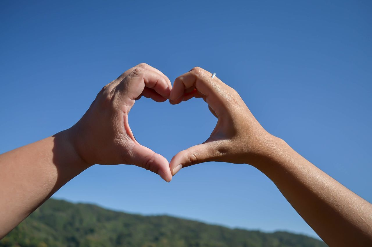 Heart Shape Human Hand Love Human Body Part Blue Clear Sky Valentine's Day  Sky Human Finger Close-up Nature Outdoors Forming Day People Unity Adult Adults Only