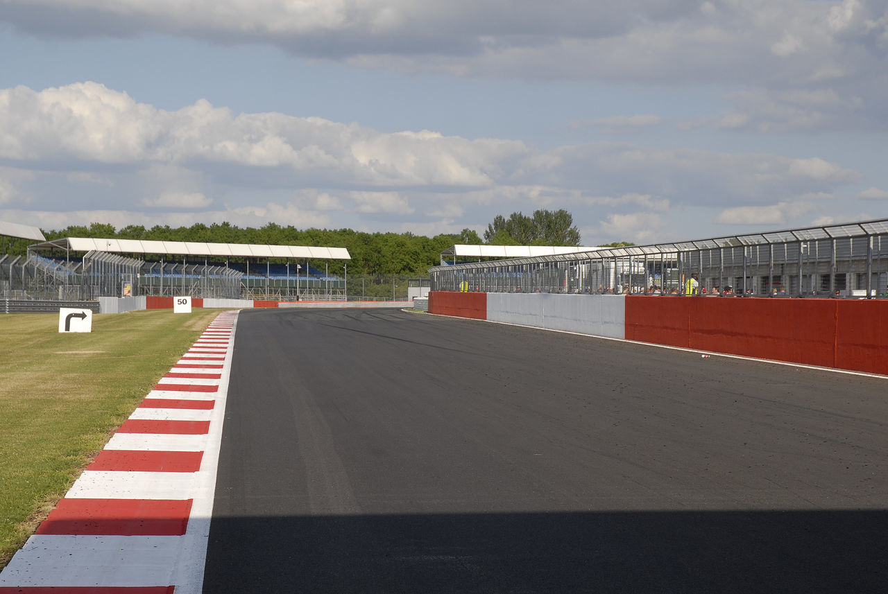 The old main-straight at Silverstone, looking toward Copse Corner Blue Close-up Cloud Cloud - Sky Direction Sign Fencing Grass Motor Vehicle No People Outdoors Race Circuit Road Seating Silver  Sky Spectator Stands Sports Race Sports Track Water Wood - Material Woodcote