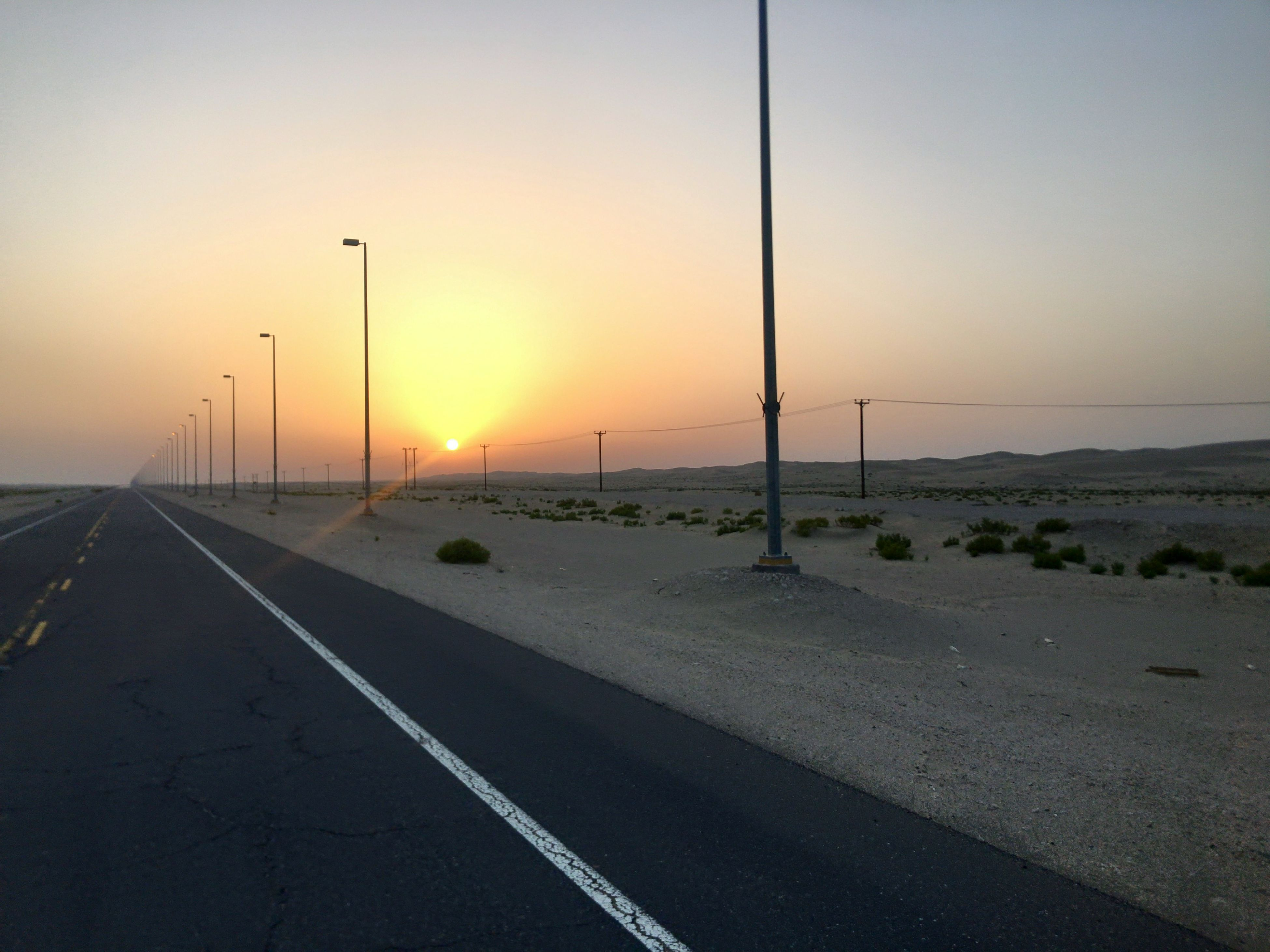 sunset, road, transportation, the way forward, scenics, nature, tranquil scene, sky, sun, no people, tranquility, outdoors, beauty in nature, clear sky, sea, water, day