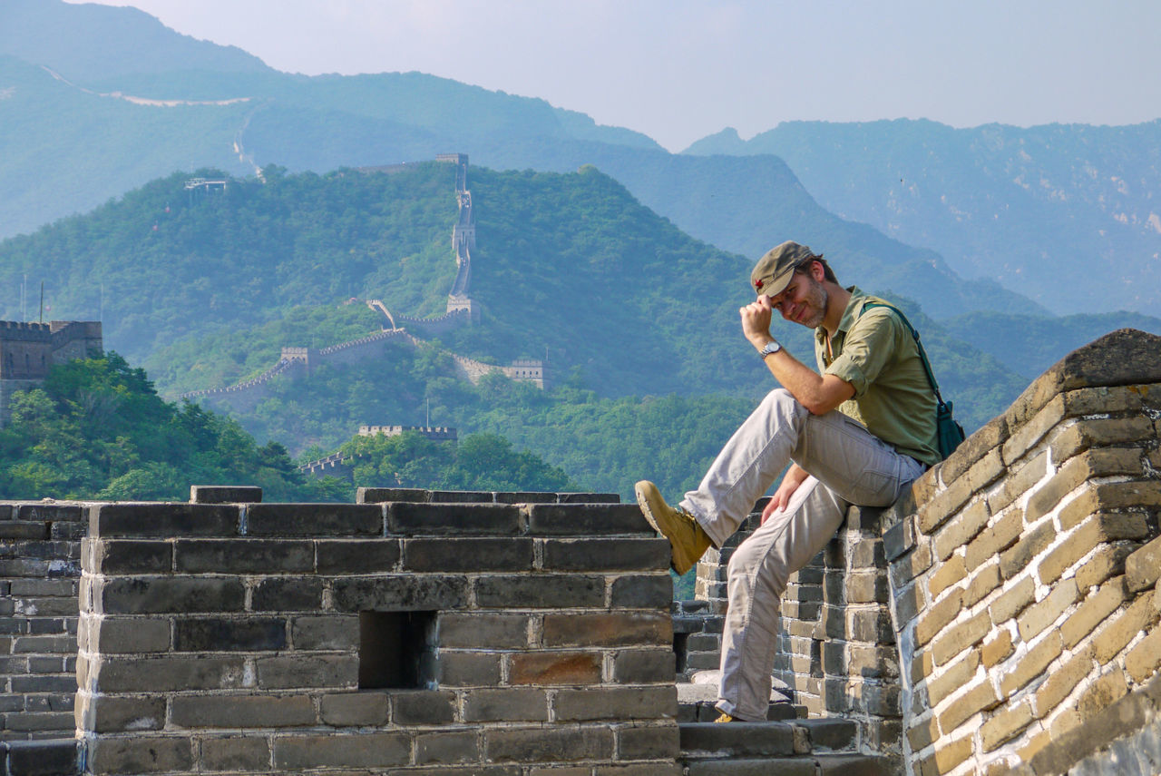 Full Length Of Smiling Man Sitting At Great Wall Of China Against Mountains