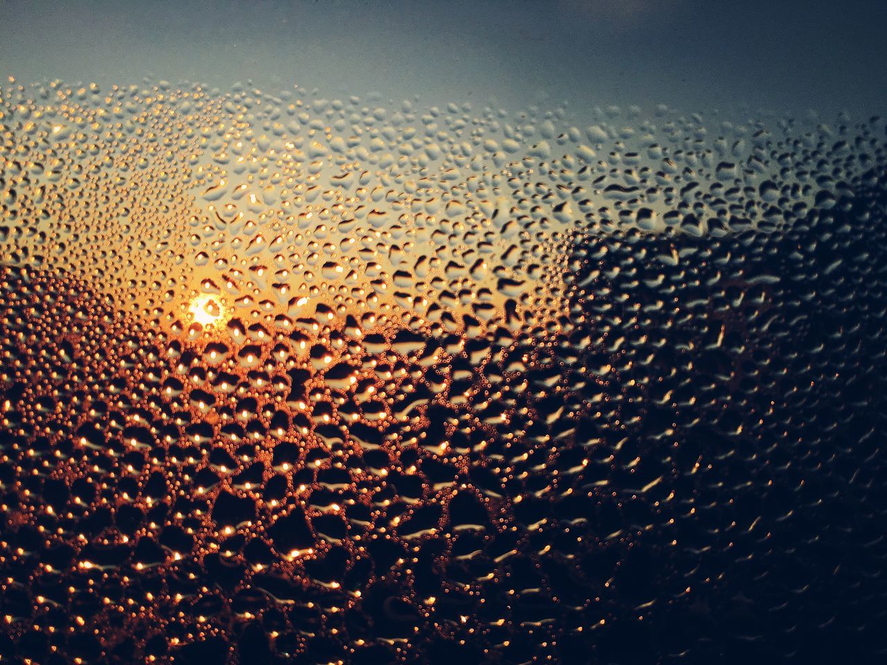Detail Shot Of Waterdrops On Glass Against Sunset