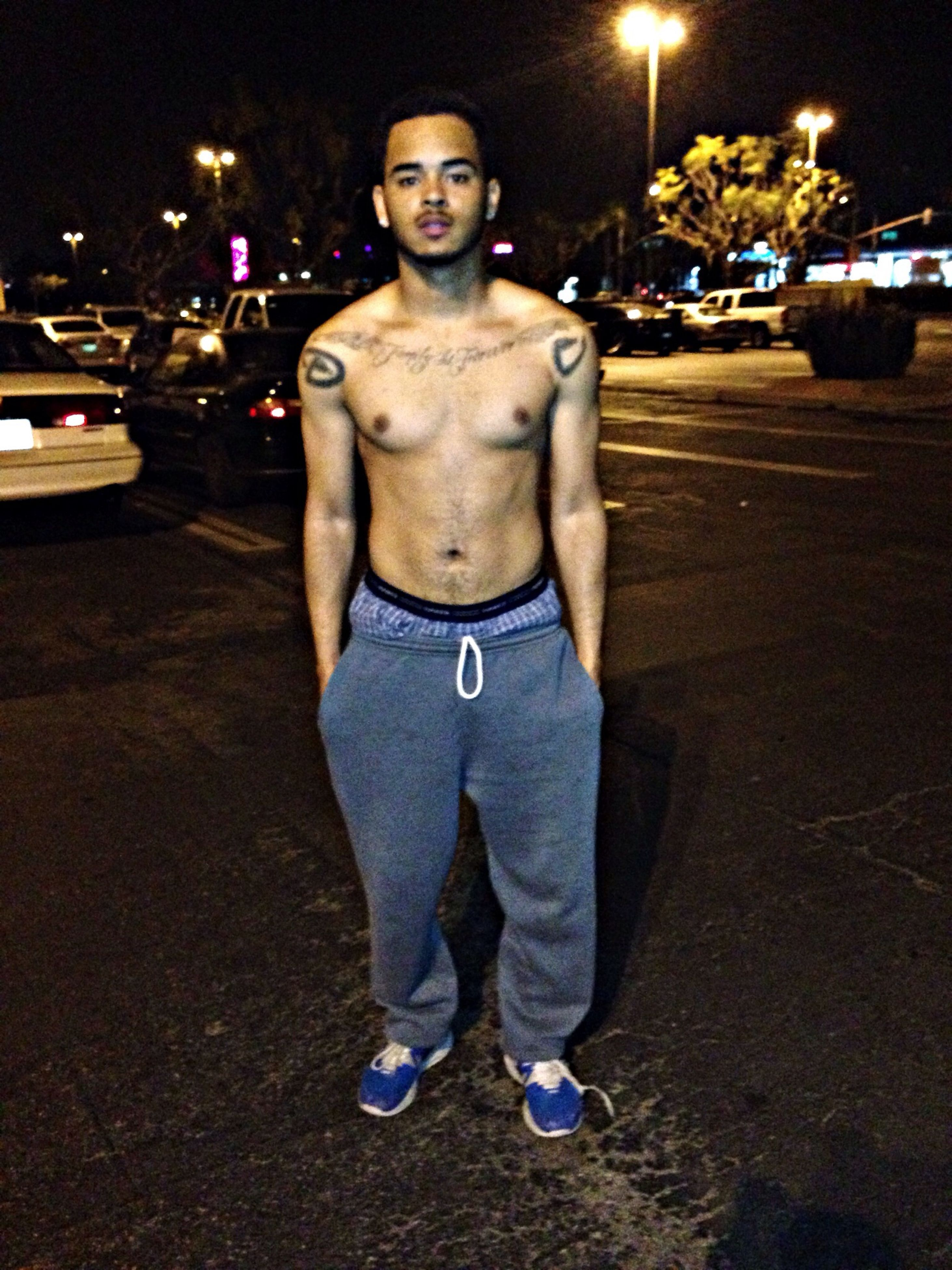 night, casual clothing, lifestyles, front view, full length, leisure activity, portrait, person, looking at camera, street, standing, illuminated, young adult, young men, incidental people, outdoors, human representation, holding