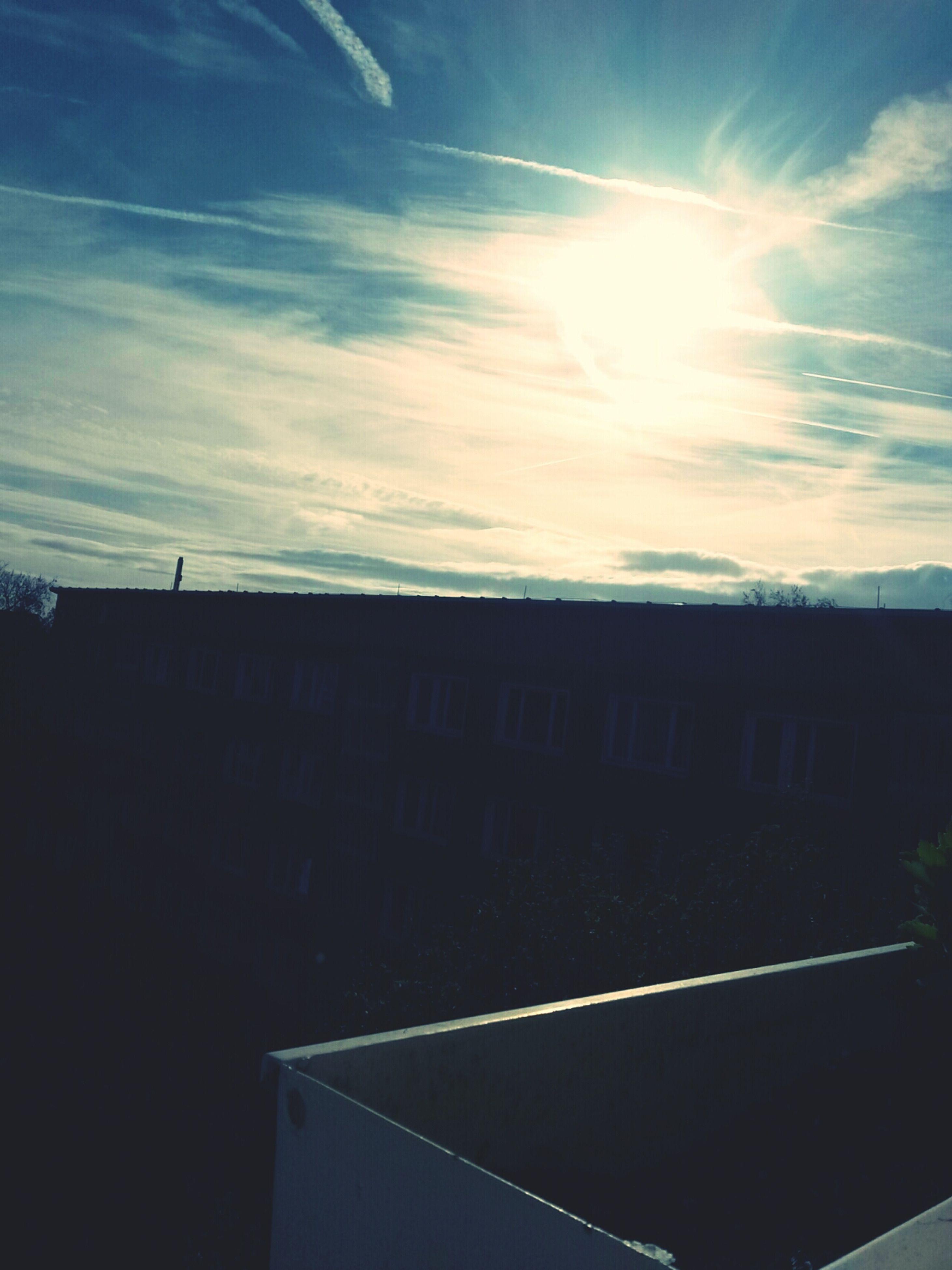 building exterior, architecture, built structure, sky, sun, sunlight, sunbeam, cloud - sky, low angle view, cloud, building, lens flare, blue, sunny, city, residential structure, residential building, outdoors, silhouette, house