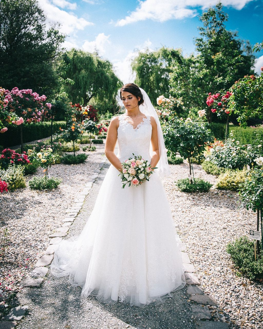 wedding, bride, wedding dress, young adult, young women, front view, real people, one person, bouquet, celebration, standing, flower, life events, women, outdoors, full length, day, lifestyles, beautiful woman, wife, nature, happiness, tree, sky, groom, adult, people