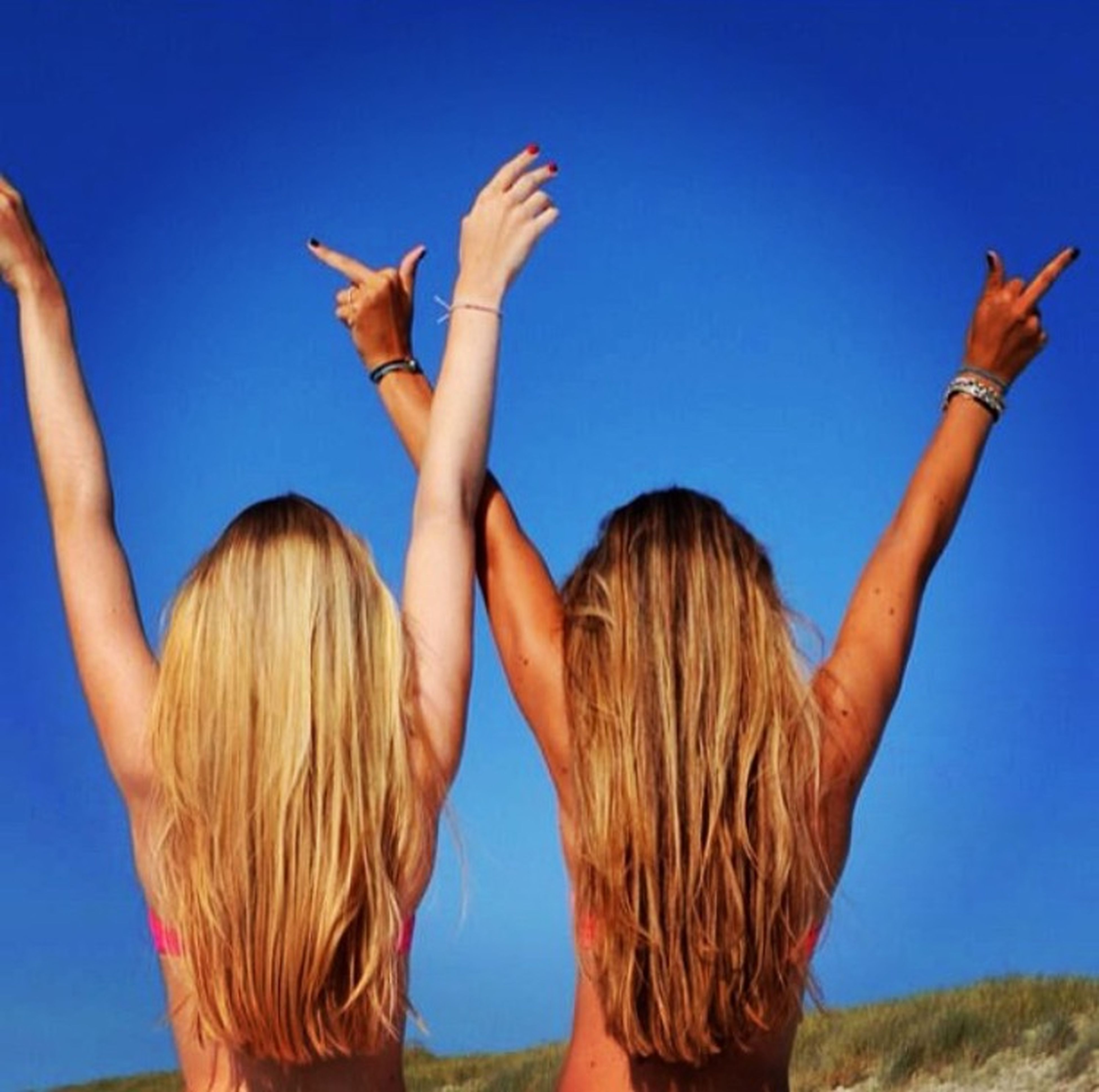 clear sky, blue, lifestyles, leisure activity, arms raised, person, young adult, young women, long hair, standing, copy space, arms outstretched, animal themes, freedom, low angle view, three quarter length, carefree, casual clothing