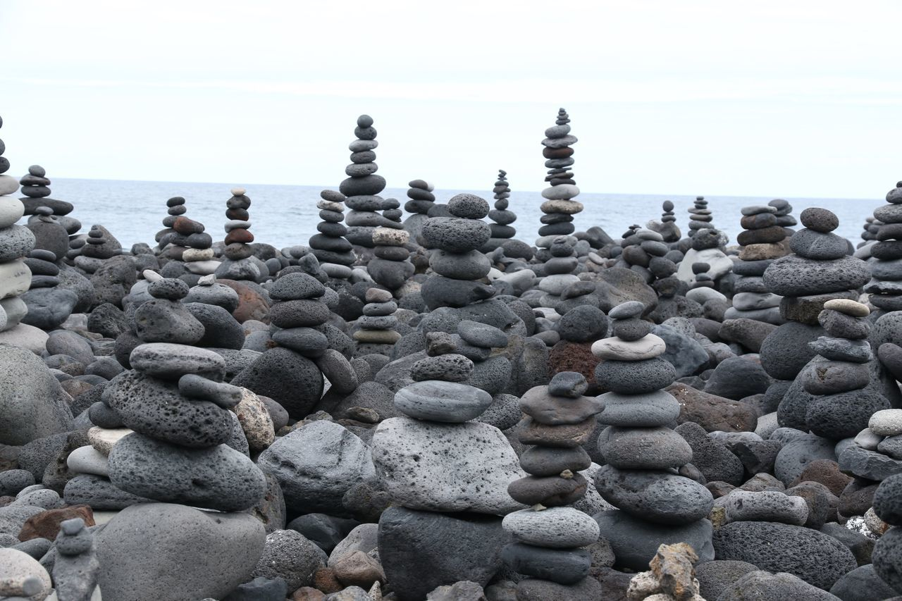 Stack Of Pebbles And Stones At Beach Against Sky