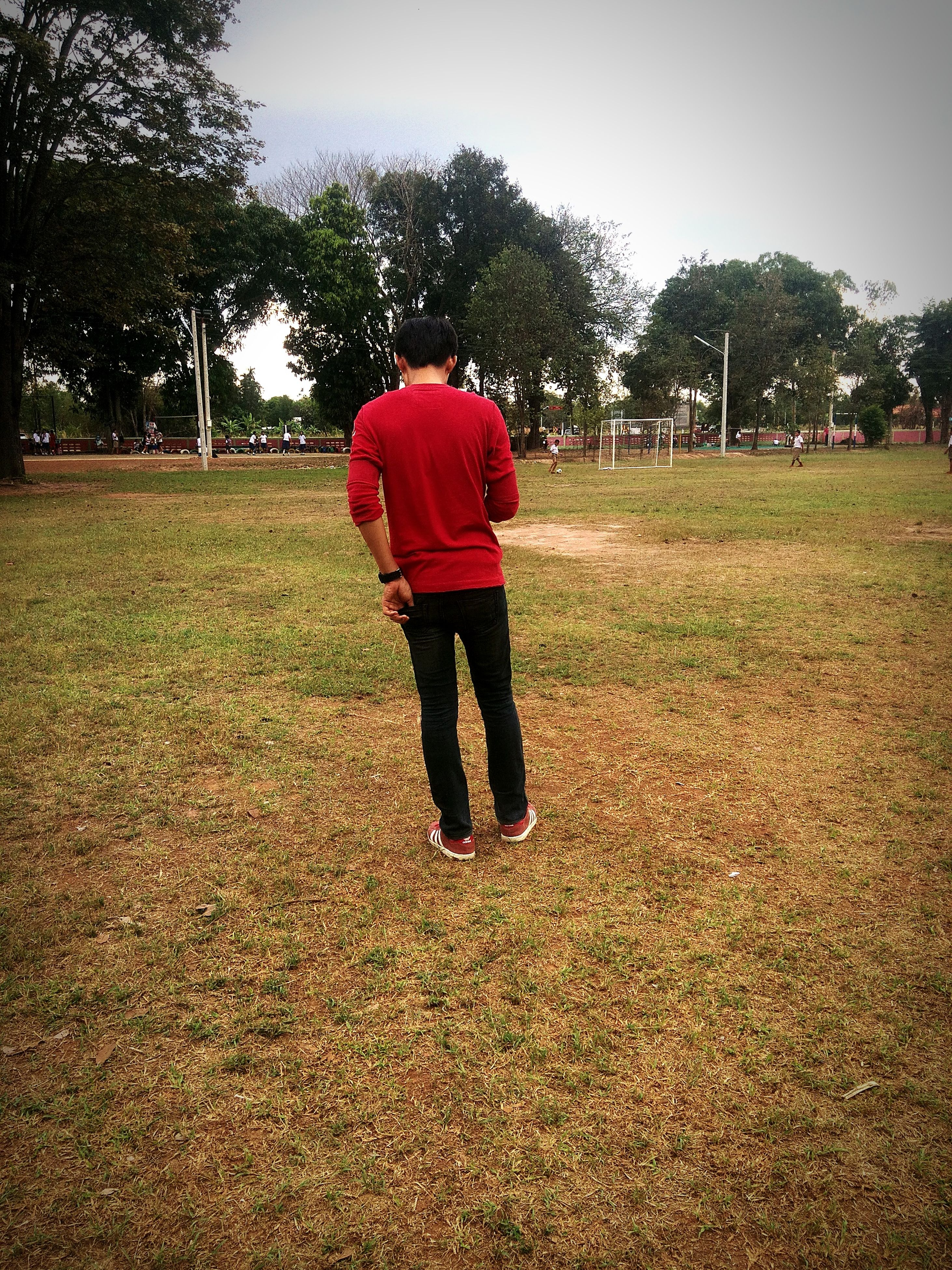 tree, full length, grass, lifestyles, leisure activity, rear view, casual clothing, childhood, field, standing, walking, grassy, tranquility, day, landscape, nature, solitude, park - man made space