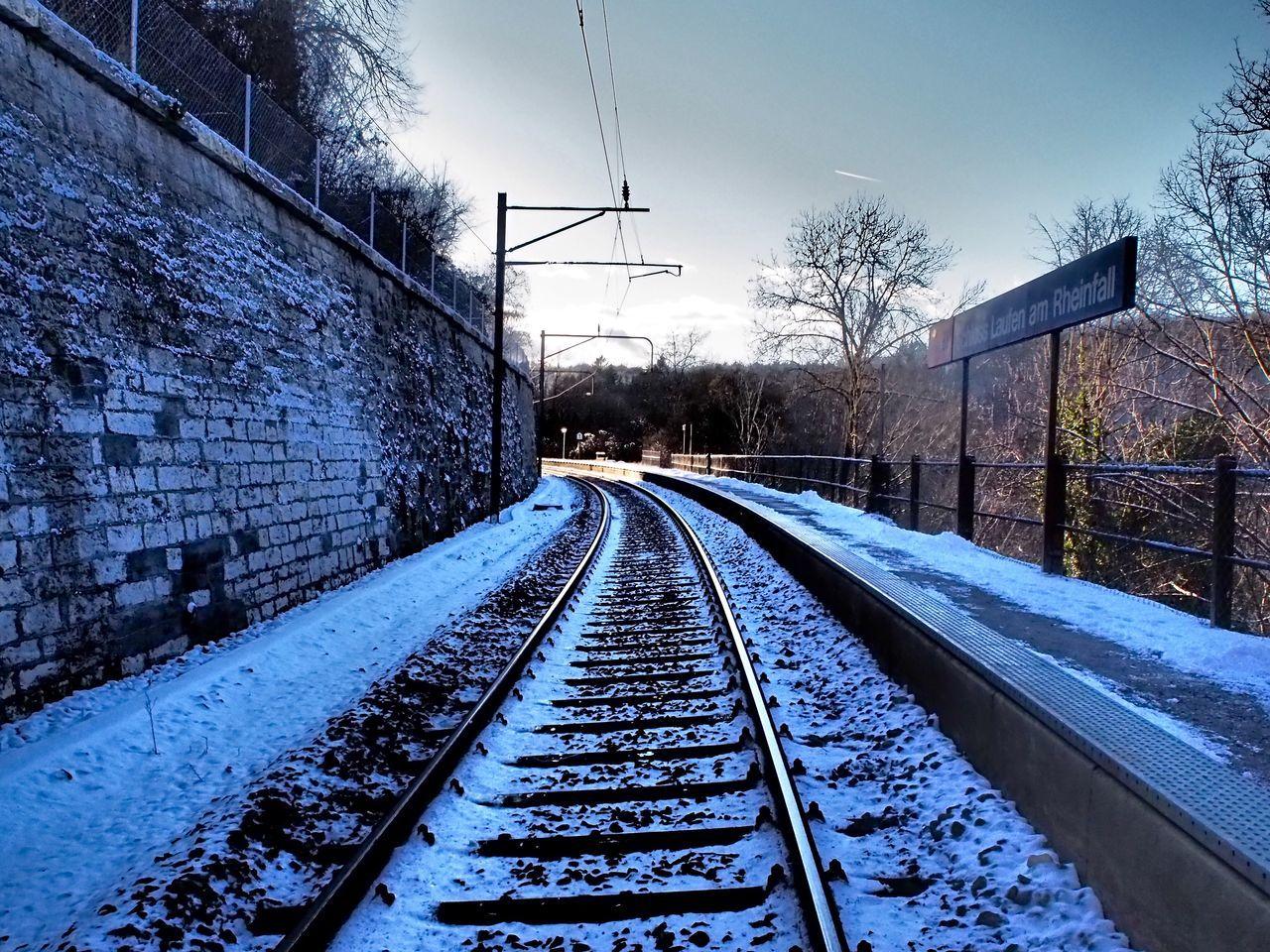 railroad track, rail transportation, cold temperature, transportation, snow, winter, no people, day, weather, railway track, the way forward, outdoors, built structure, bare tree, architecture, sky, tree, nature