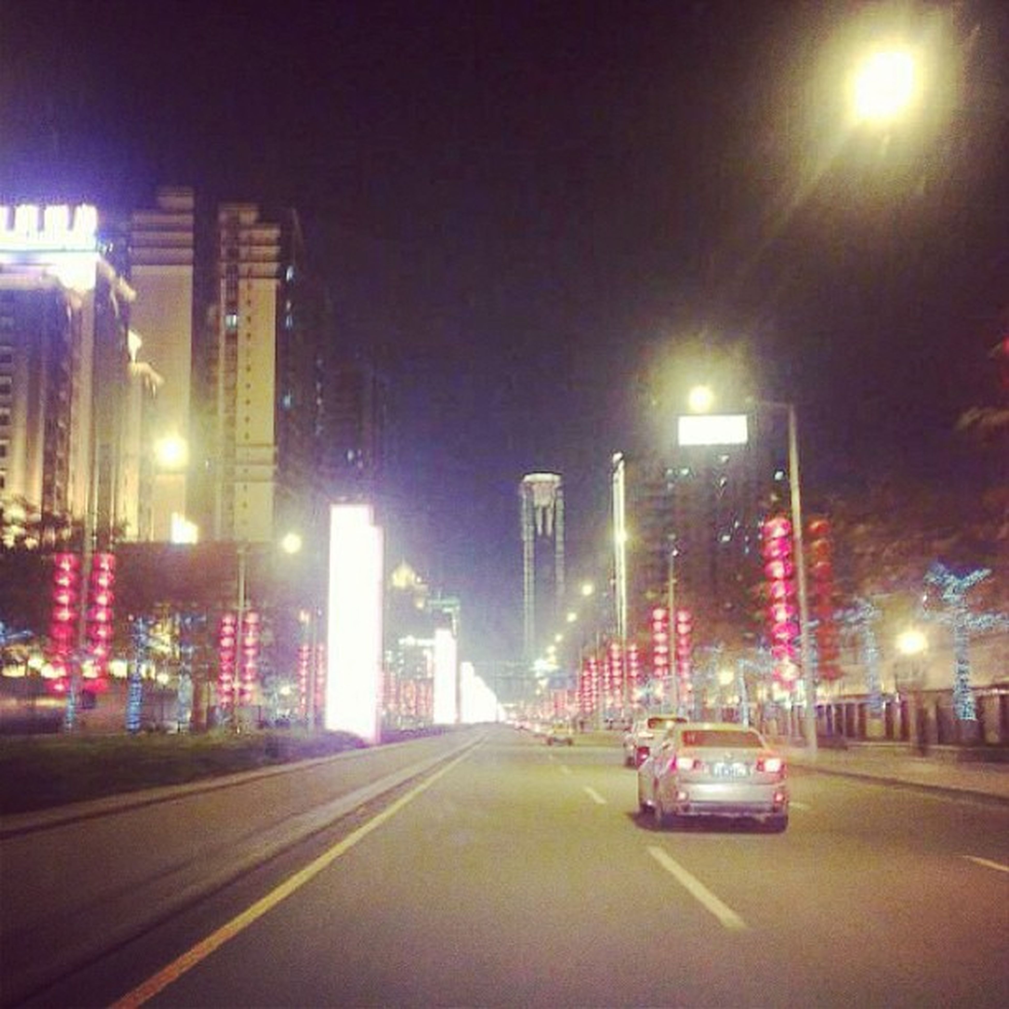city, building exterior, illuminated, architecture, built structure, transportation, night, skyscraper, car, street, road, modern, office building, land vehicle, city life, street light, the way forward, city street, tall - high, cityscape