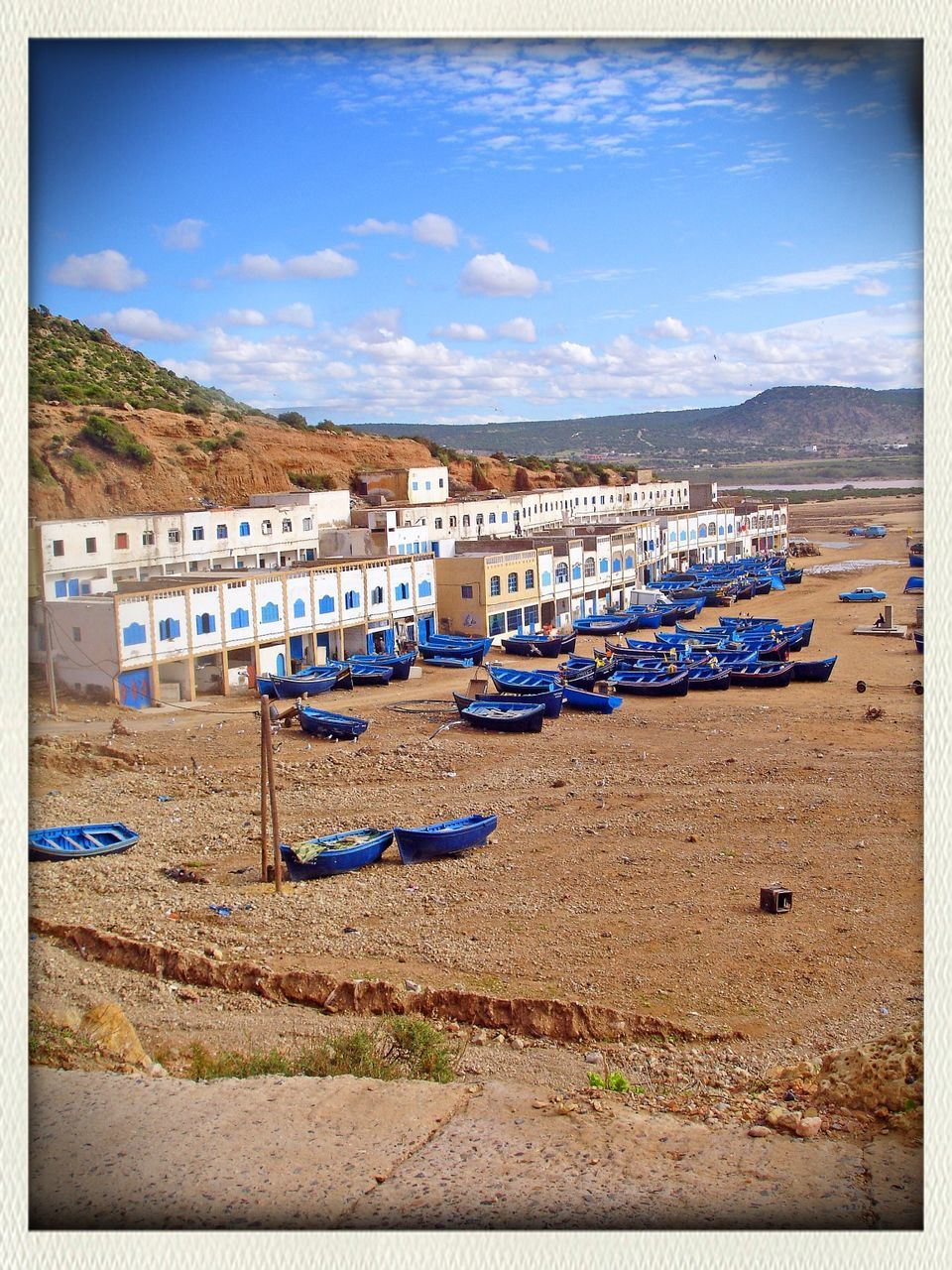 High angle view of boats moored on sand by buildings