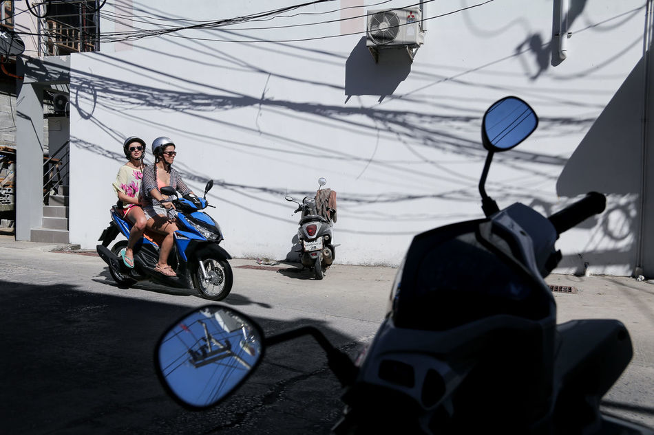 Tourists in Haad Rin town on Phangan island in the Gulf of Thailand, known as the original location of the (in)famous Full Moon Parties. Backpacking Bike Cables Day Electricity  Full Moon Party Haad Rin Horizontal Koh Phangan Mode Of Transport Motorbike Only Women Outdoors People Person Scooter Sky Street Photography Streetphoto Streetphotography Tourism Tourists Transportation Treveling Women Around The World