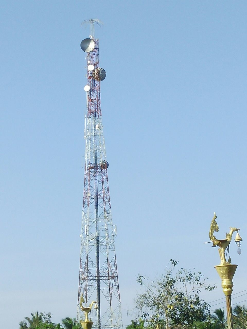 tall - high, low angle view, tower, tree, clear sky, day, no people, architecture, built structure, communication, outdoors, blue, telecommunications equipment, sky, technology, nature
