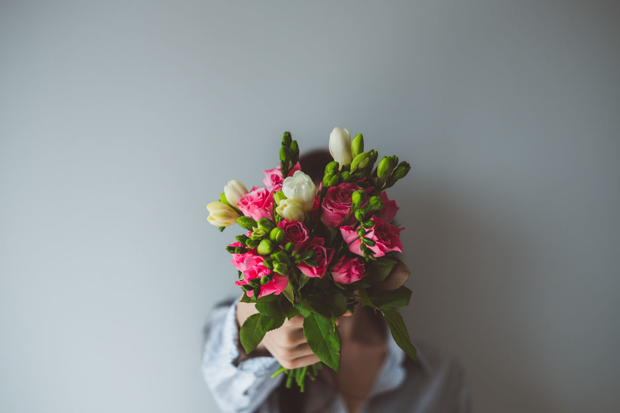 flower, human hand, studio shot, human body part, copy space, one person, holding, fragility, petal, freshness, bouquet, real people, gray background, flower head, white background, beauty in nature, close-up, nature, day, florist, people
