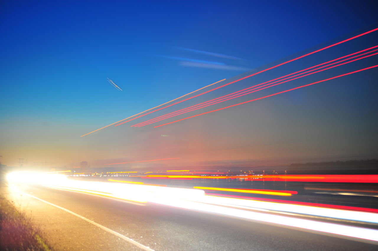 speed, transportation, motion, light trail, long exposure, blurred motion, illuminated, night, mode of transport, multi colored, no people, outdoors, sky, road, sunset, high street