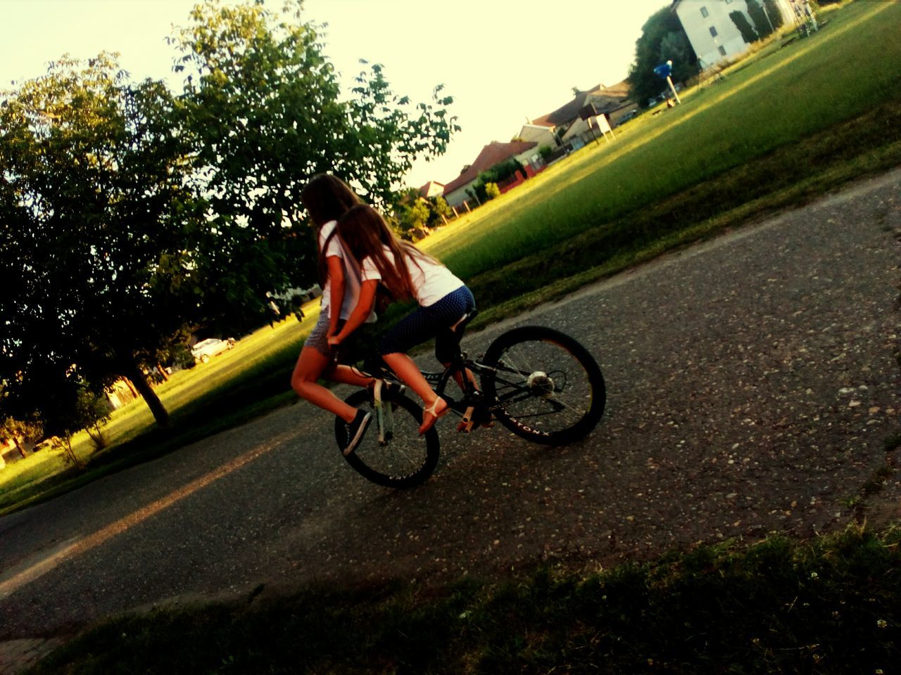 bicycle, riding, transportation, real people, cycling, one person, mode of transport, full length, leisure activity, lifestyles, land vehicle, day, motion, outdoors, tree, road, helmet, cycling helmet, sport, mountain bike, bmx cycling, extreme sports, nature, young women, young adult, biker, sky, people