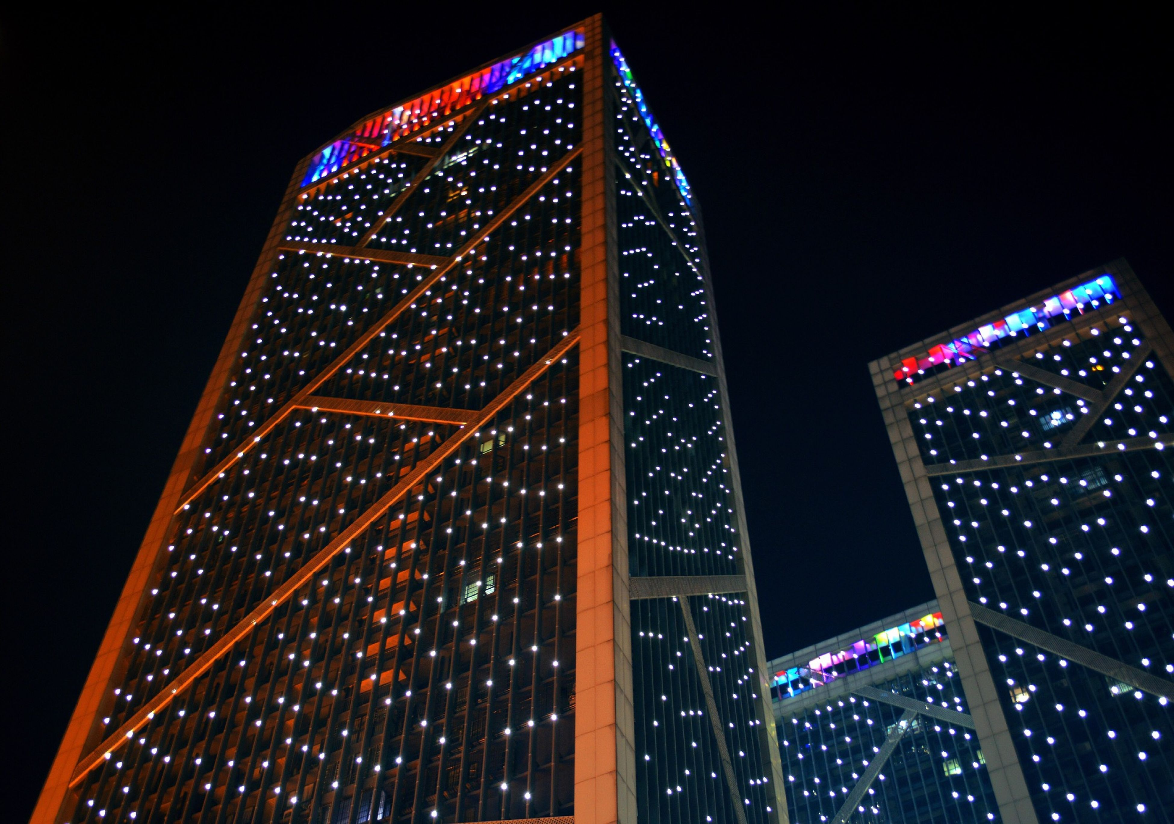 illuminated, low angle view, night, architecture, built structure, tower, building exterior, tall - high, modern, skyscraper, city, lighting equipment, clear sky, sky, no people, pattern, famous place, capital cities, outdoors, travel destinations