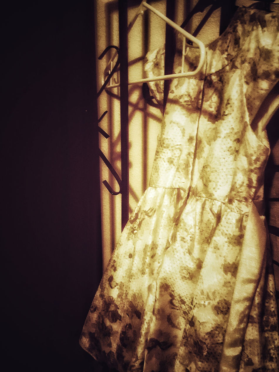 A young girl's dress, bathed in a creepy light. Dress Hanging Up Hanger Hangers Girls Dress Girl Clothes Clothing Dress Hung Up Hanging Dress Little Girl Dress Dark Darkness And Light Shadows Yellow Glow Eerie Tailored To You Noir Flower Pattern Monochromatic Monochrome White Dress Flower Dress Dressy Closet
