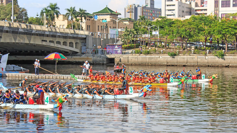 Kaohsiung, Taiwan, June 19, 2015: Boats racing in the Love River for the Dragon Boat Festival in Kaohsiung, Taiwan. The Dragon boats are the basis of the team paddling sport of dragon boat racing, a watersport which has its roots in an ancient folk ritual of contending villagers, which has been held for over 2000 years throughout southern China. For competition events, dragon boats are generally rigged with decorative Chinese dragon heads and tails. At other times (such as during training), decorative regalia is usually removed, although the drum often remains aboard for drummers to practice. Dragon boat races are traditionally held as part of the annual Duanwu Festival or Duen Ng observance in China and Taiwan. Architecture ASIA Building Exterior Built Structure China City Competition Day Dragon Boat Festival Hot Kaohsiung, Taiwan Large Group Of People Leisure Activity Lifestyles Love River Mixed Age Range Outdoors Rippled River Summer Taiwan Tree Tropics Water Waterfront