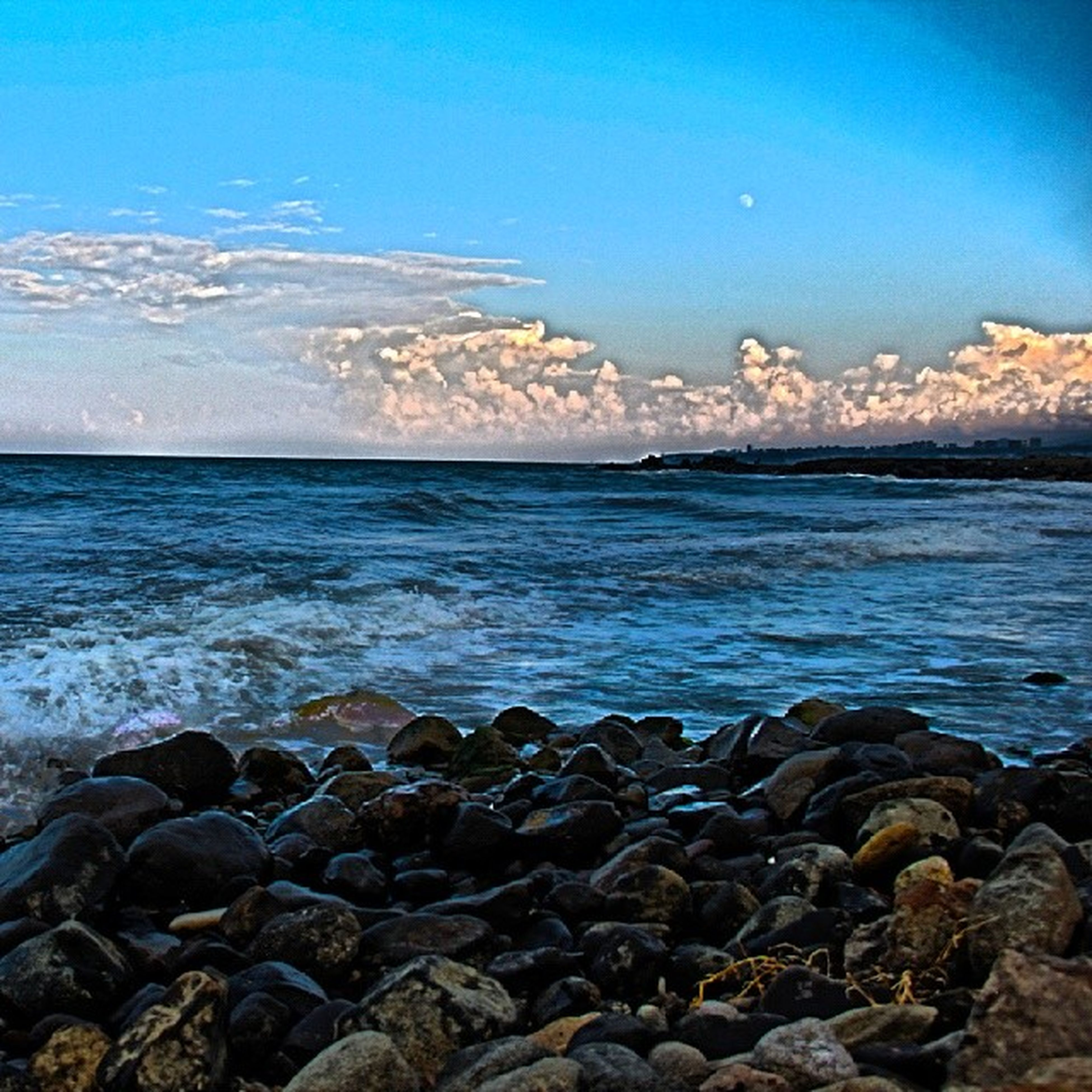 water, sea, scenics, tranquil scene, beauty in nature, tranquility, beach, horizon over water, blue, sky, nature, rock - object, shore, idyllic, stone - object, wave, clear sky, pebble, outdoors, remote