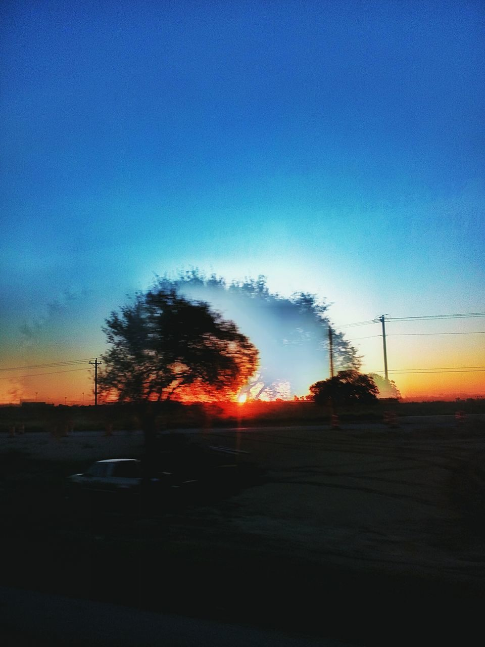 sunset, silhouette, car, sky, no people, road, blue, tree, land vehicle, outdoors, nature, electricity pylon, clear sky, day