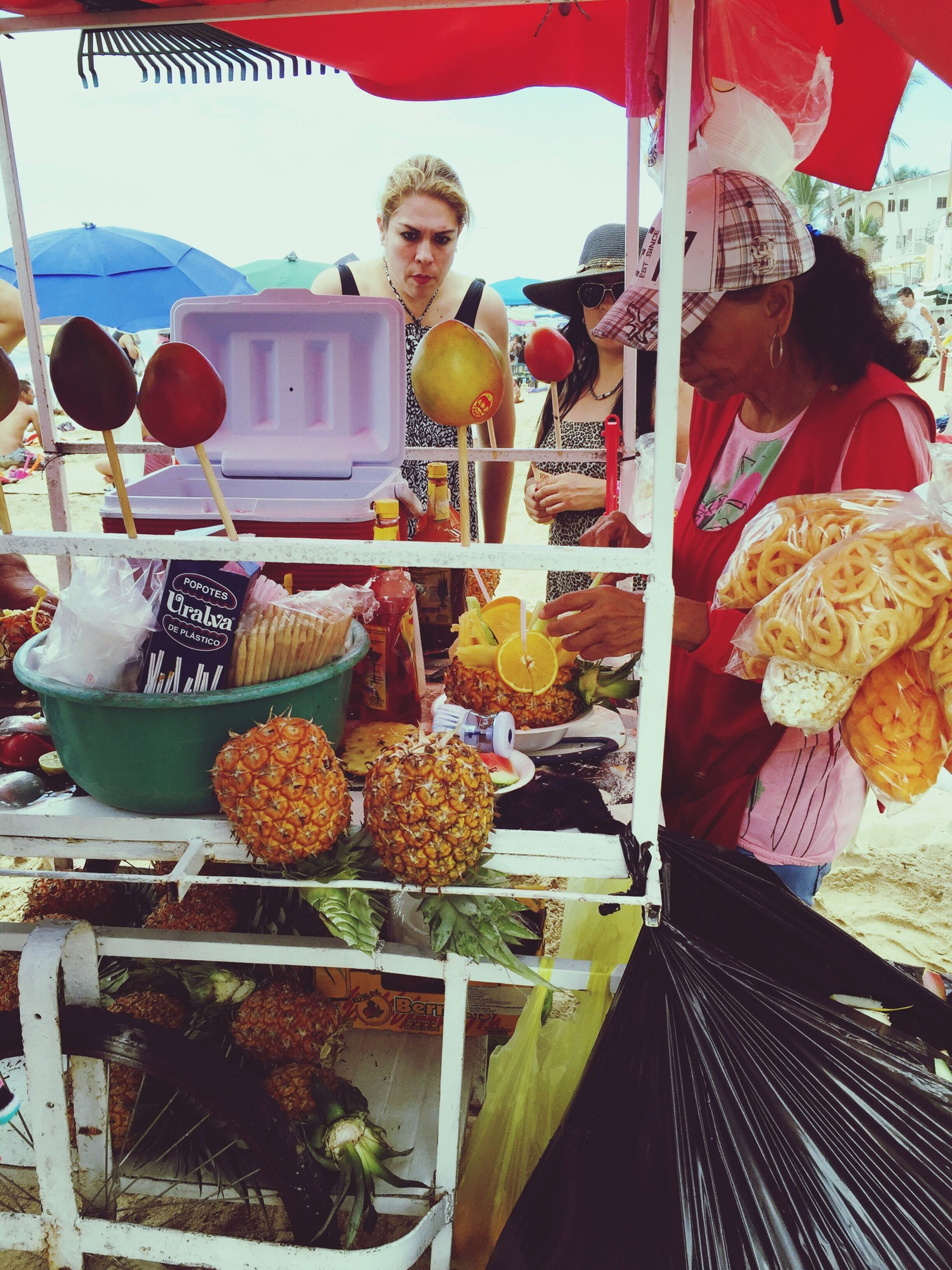 food and drink, food, lifestyles, freshness, healthy eating, retail, leisure activity, fruit, casual clothing, for sale, holding, variation, standing, market stall, choice, indoors, market, large group of objects